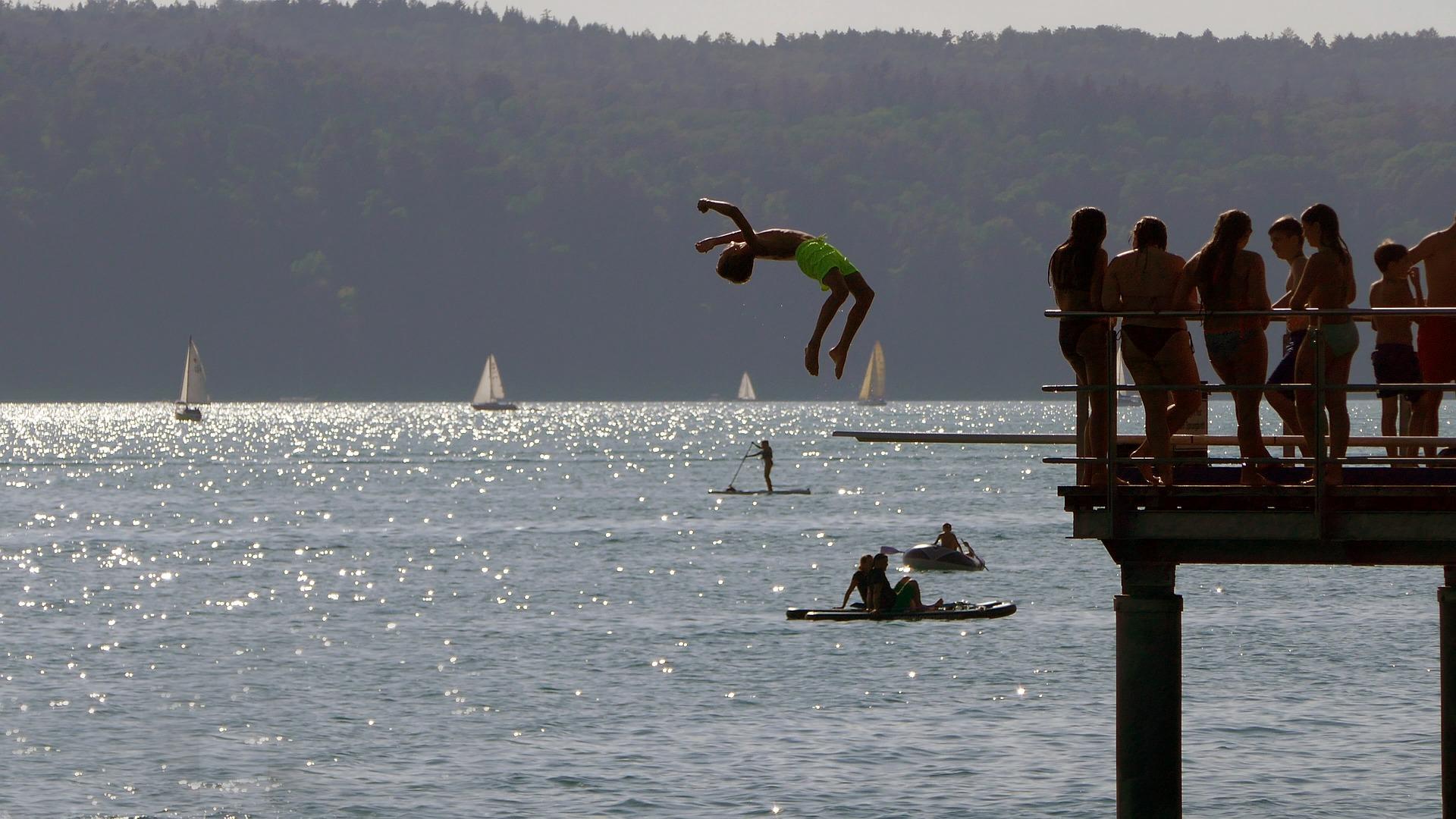 Ein Junge springt rückwärts von einem Steg in einen See. Im Hintergrund sind Segelboote und Stand-Up-Paddler zu sehen.