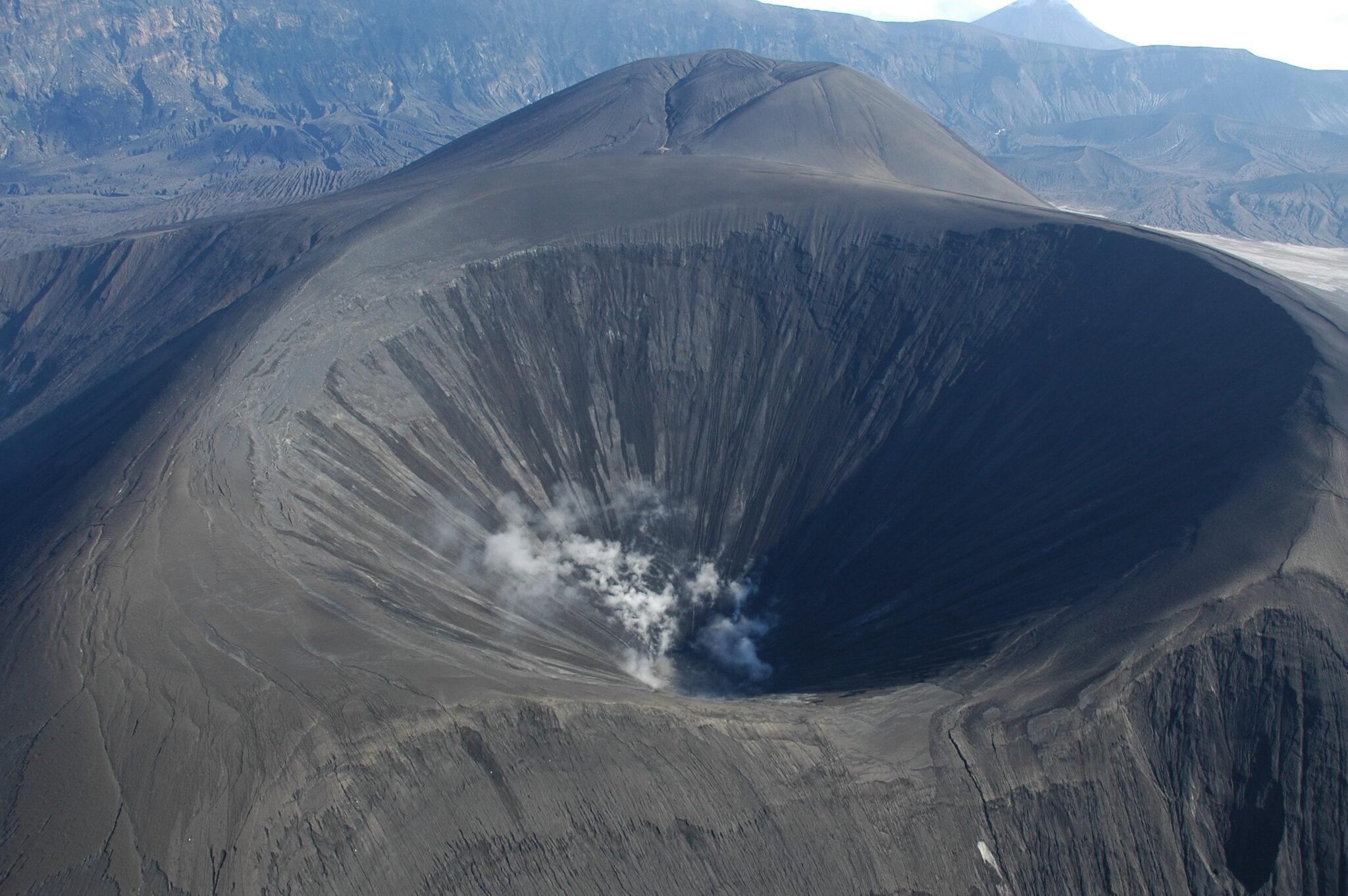 ein neuer Krater des Vulkans Okomok in Alaska. Er ist dunkelgrau und es steigen kleine Rauchwölkchen auf