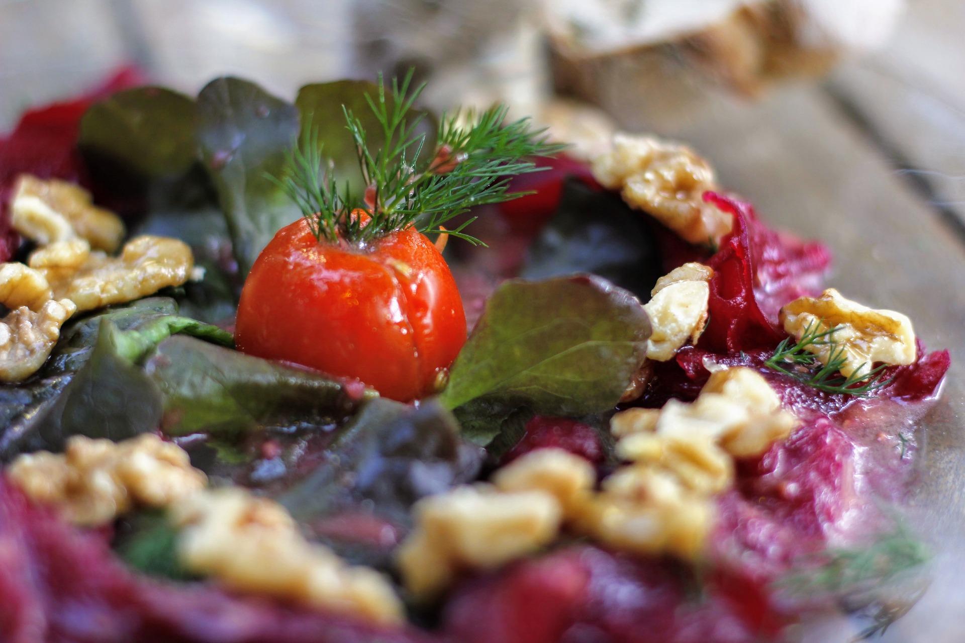 Eine Nahaufnahme eines Salates mit Rinden, Baumnüssen, kleinen Salatblättern und einer mit Dill dekorierten Kirschtomate