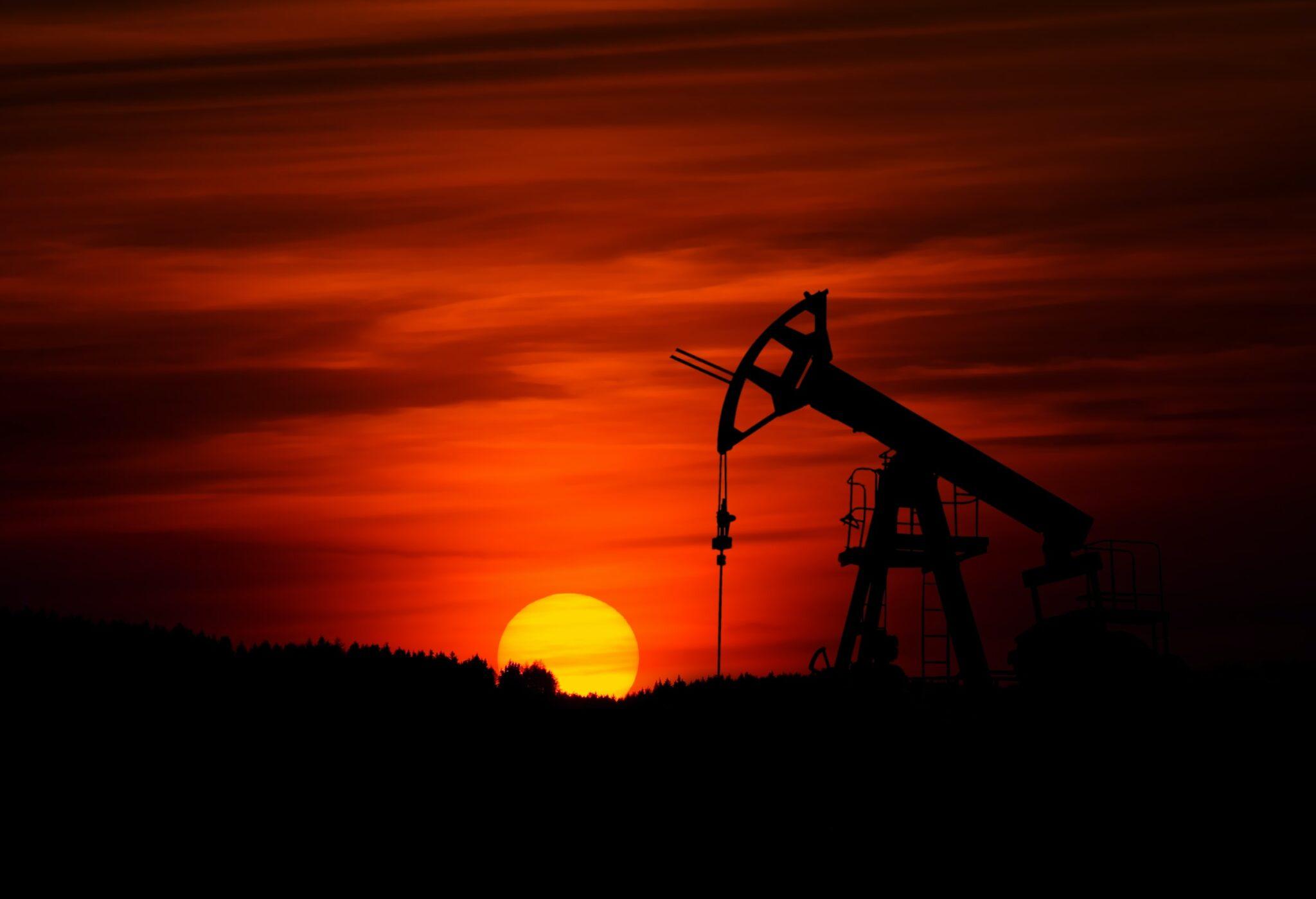 Eine Ölförderpumpe als Schattenriss vor einem intensiv roten Sonnenuntergang