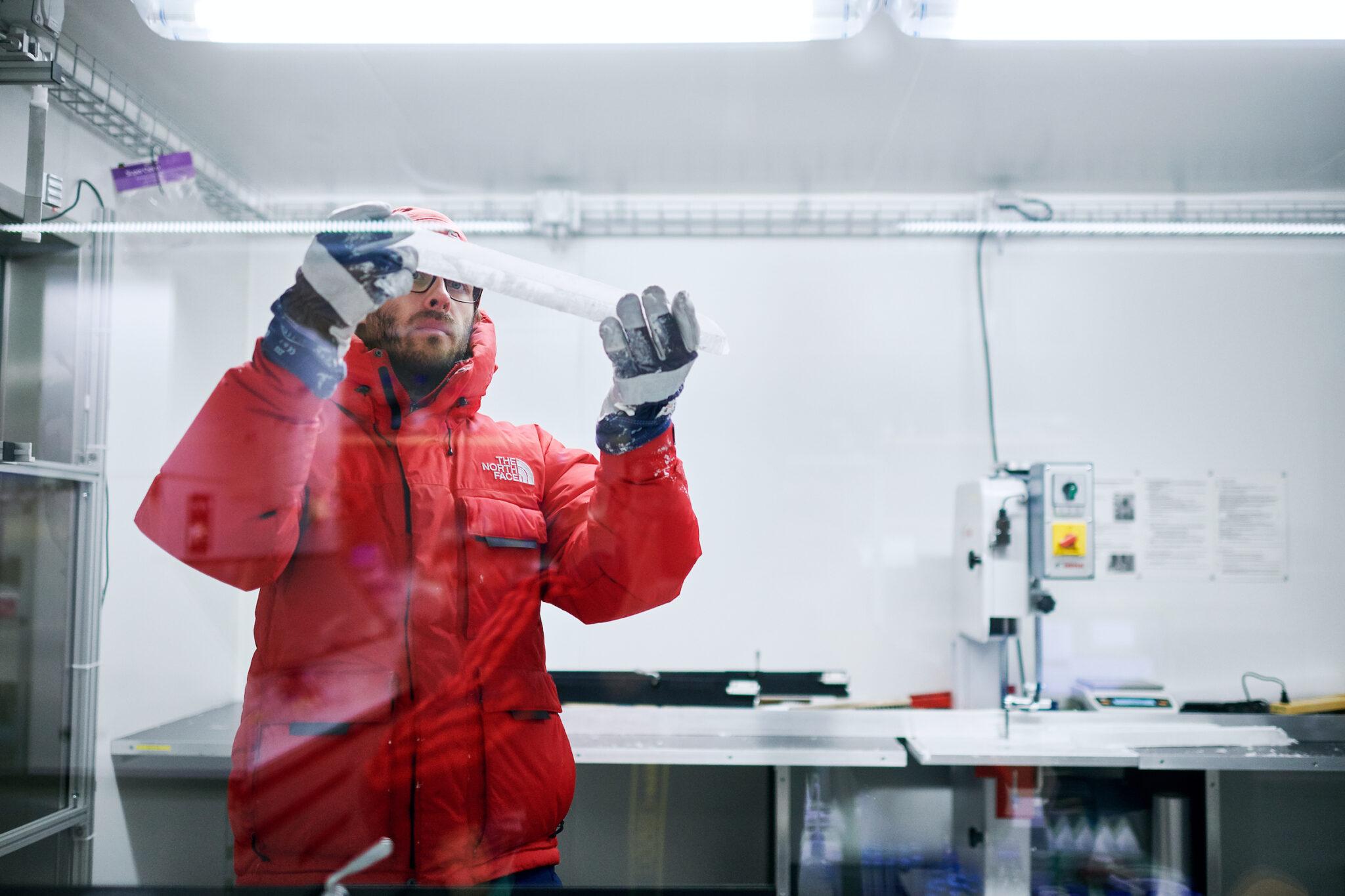 Ein Forscher in roter Winterjacke und blau-weiss gestreiften Handschuhen hält einen Eisbohrkernen in den Händen.