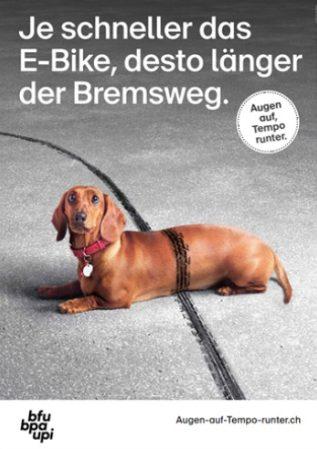 Plakat mit einem Velobremsstreifen, der über einen Hund geht, der auf dem Boden liegt und den Kopf hebt
