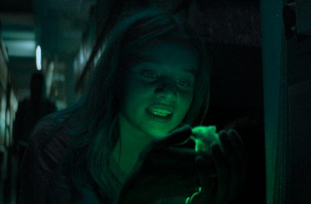 Ein Mädchen hält eine Maus in den Händen, das ganze ist grün beleuchtet.