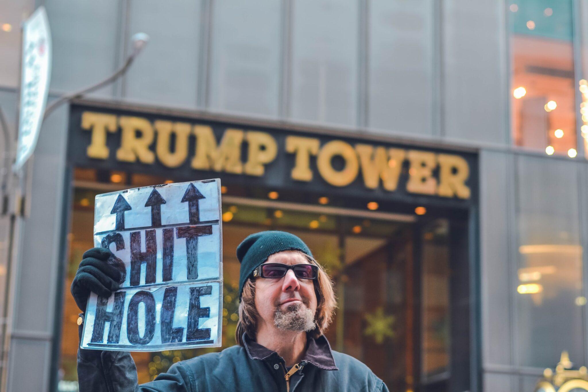 """Ein bärtiger mittelalter Mann mit Mütze steht vor dem Turm Tower und hält ein Schild mit """"Shit Hole"""" Aufschrift hoch."""