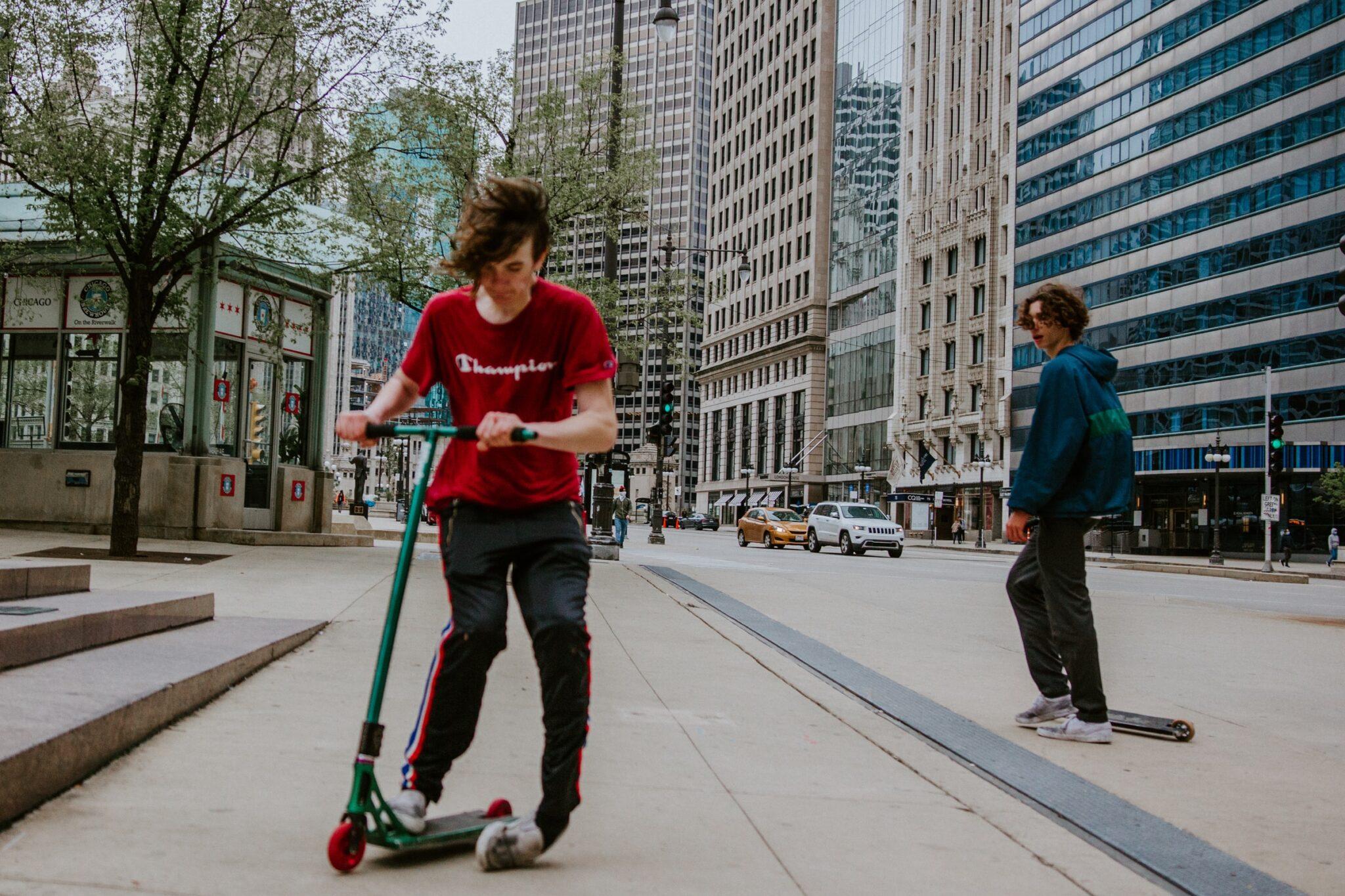 Ein junger Skates in rotem T-Shirt und dunkler Hose steht mit dem rechten Bein auf einem Tretroller und knickt mit dem linken Knöchel auf dem Boden um.