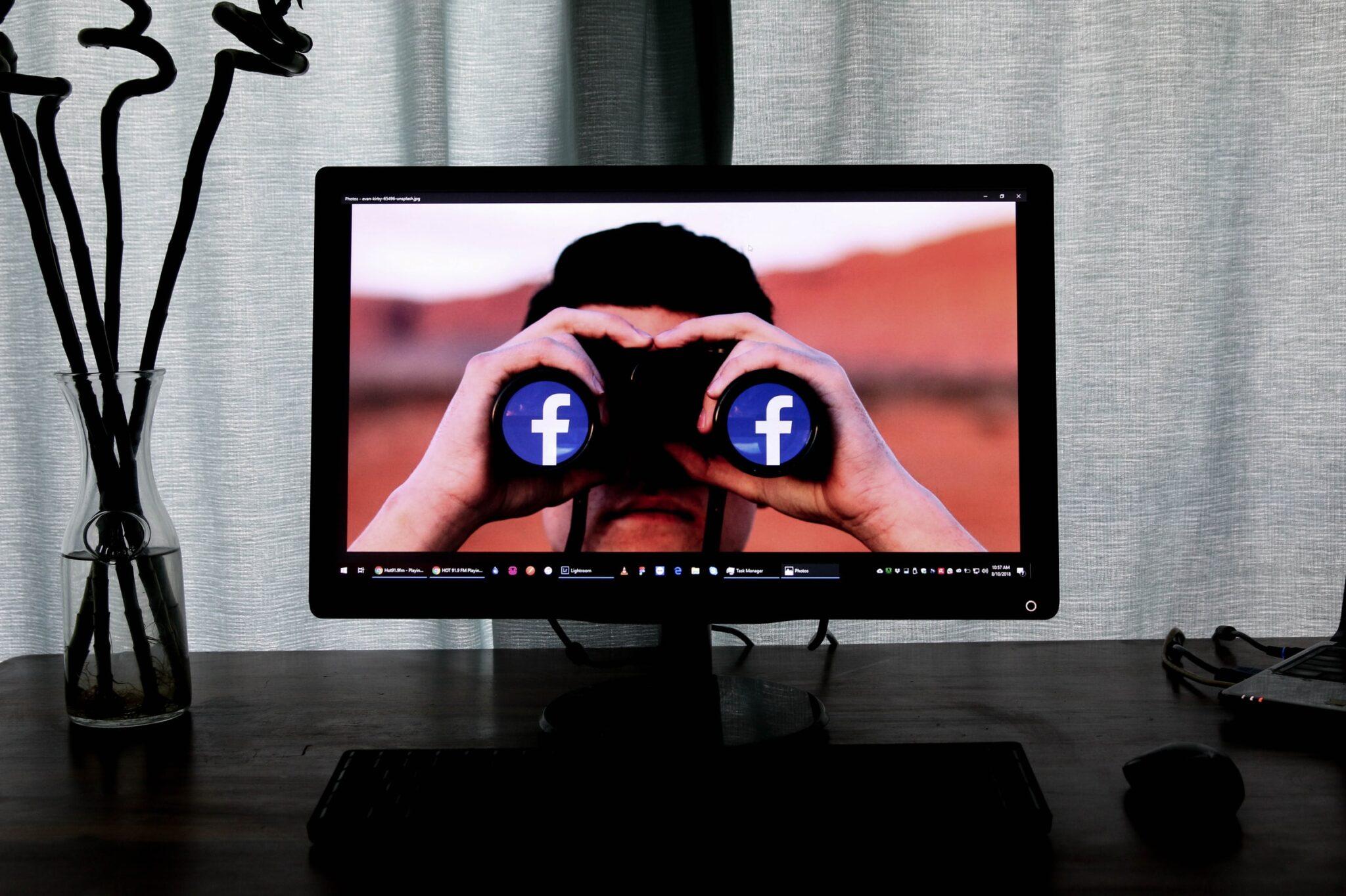 Mann mit Fernglas, auf dem Facebook-F auf den Linsen zu sehen sind, ist auf einem Bildschirm zu sehen, der auf einem Tisch steht.