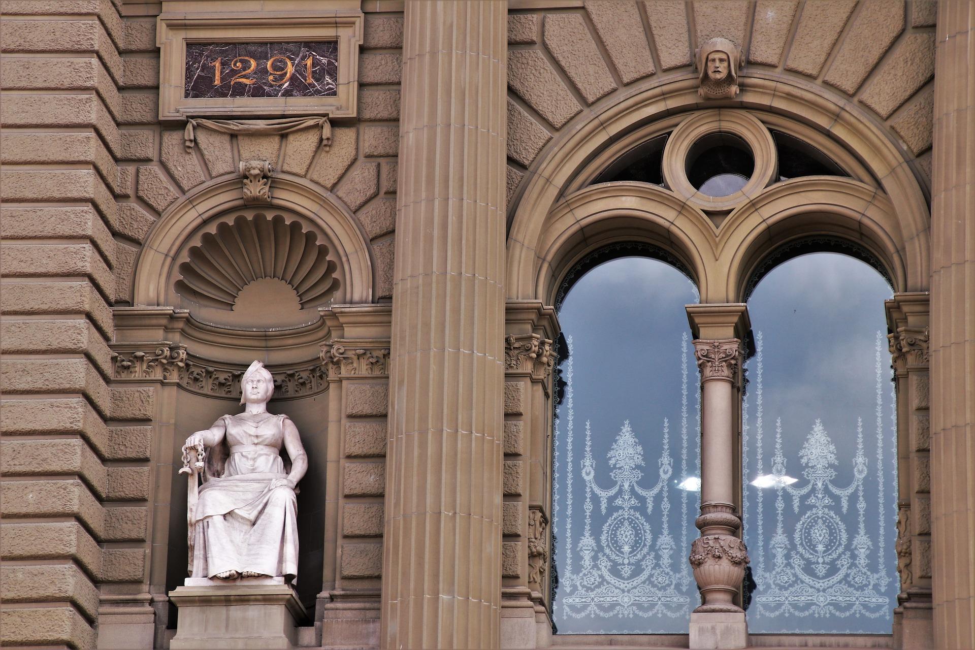 Das Bundeshaus in Bern in Nahaufnahme. Links eine Statue und rechts ein Fenster