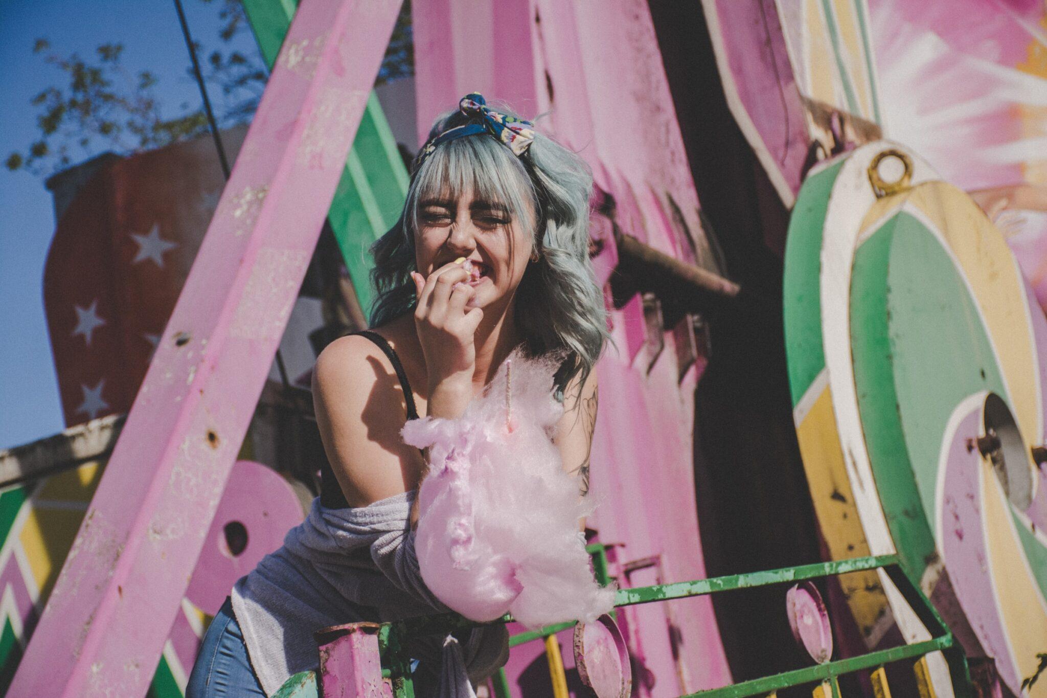 Eine junge Frau mit pastelltürkisfarbenen Haaren isst lachend rosa Zuckerwatte vor einer jahrmarktsartigen rosa Konstruktion.