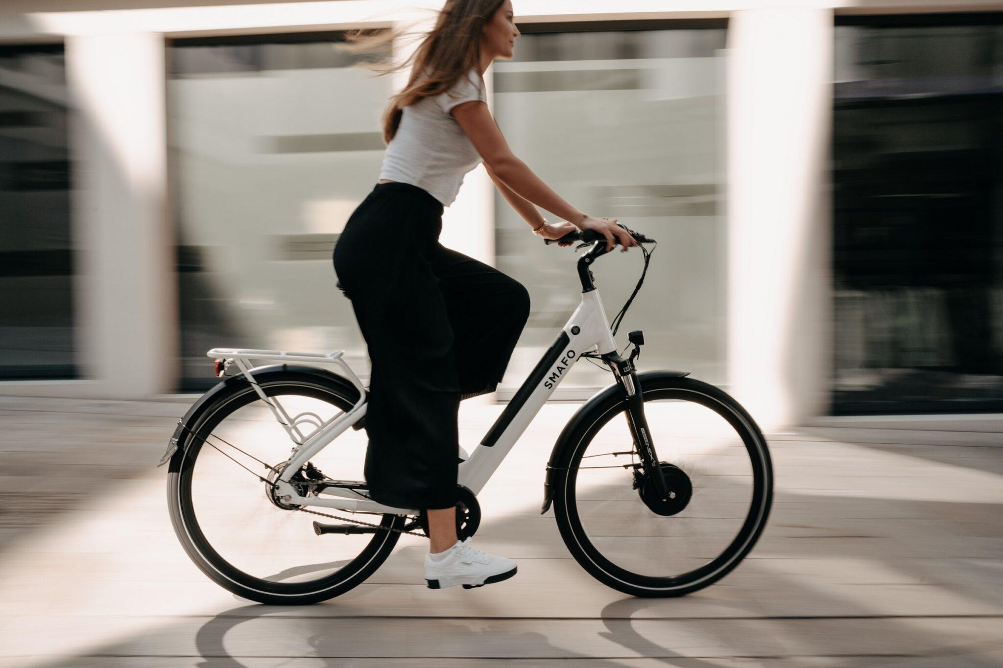 Frau mit weissem Shirt und schwarzer flattriger Hose fährt auf einem weissen E-Bike