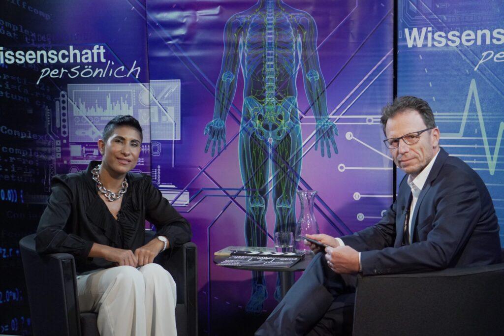 Katja Rost sitzt links mit einer weissen Hose und einem schwarzen Oberteil. Beat Glogger sitzt rechts in einem grauen Anzug.