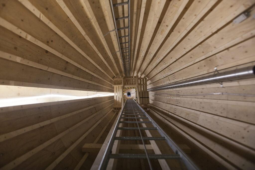 Blick von innen nach oben in die Holzkonstruktion. Es führen 2 Leitern nach oben.