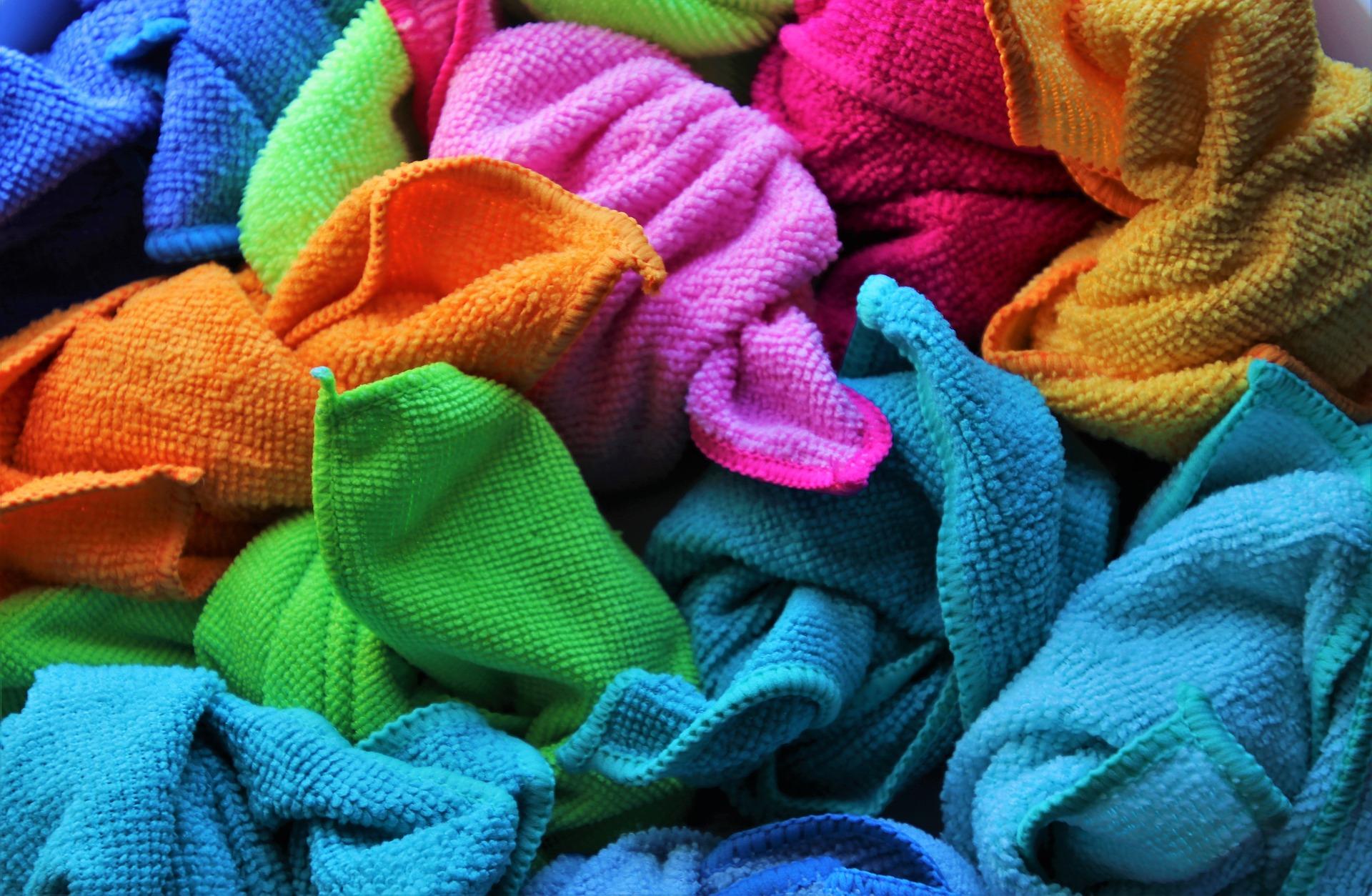 Zerknüllte bunte Mikrofaserlappen in blau, grün, orange und pinktönen.