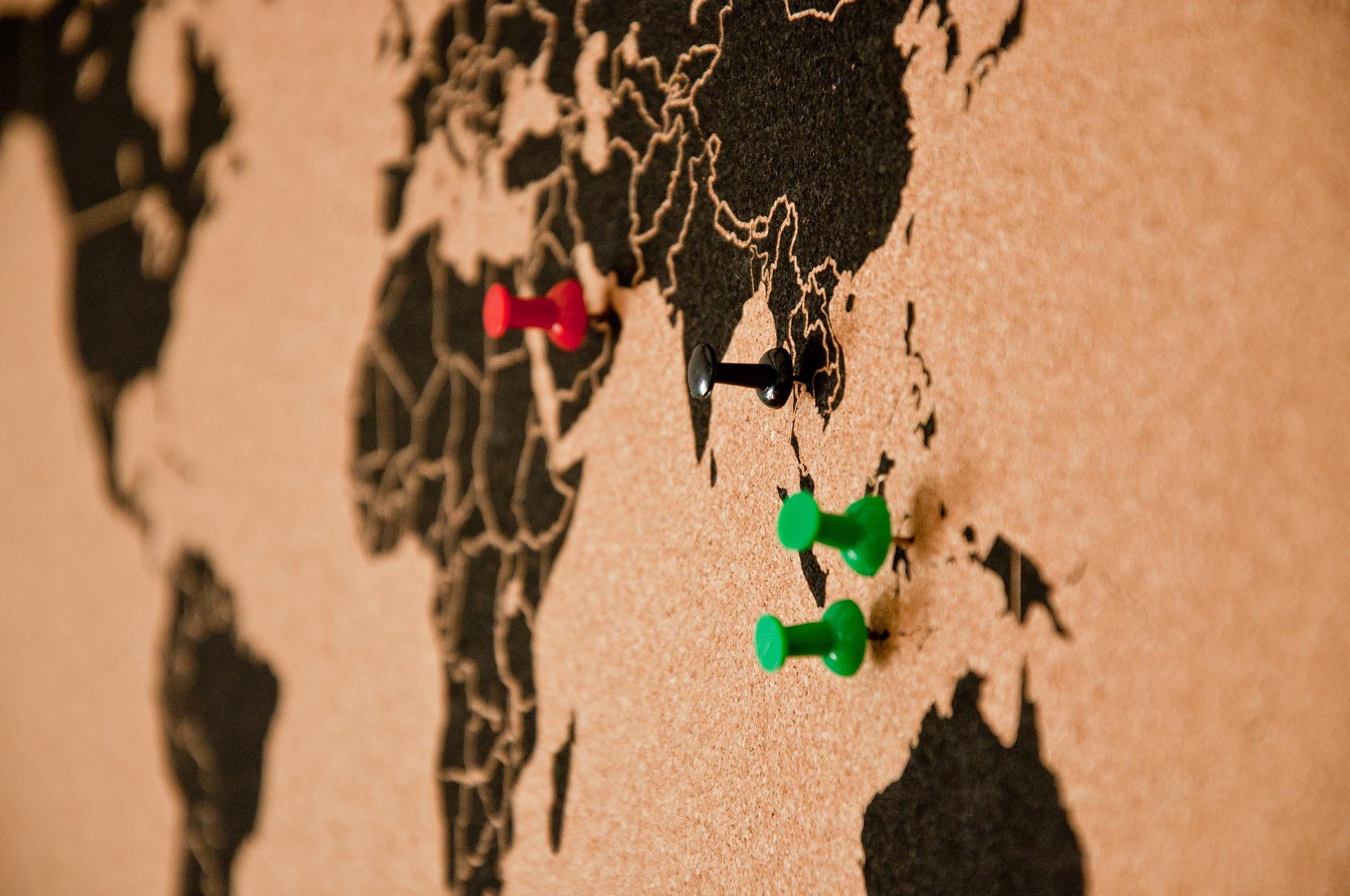 Eine Pinnwand, auf der Man vor allem Asien, Afrika und Neuseeland sieht, schlichte schwarze Umrisse auf hellbraunem Kork. Vier Pins stecken in unterschiedlichen Ländern.