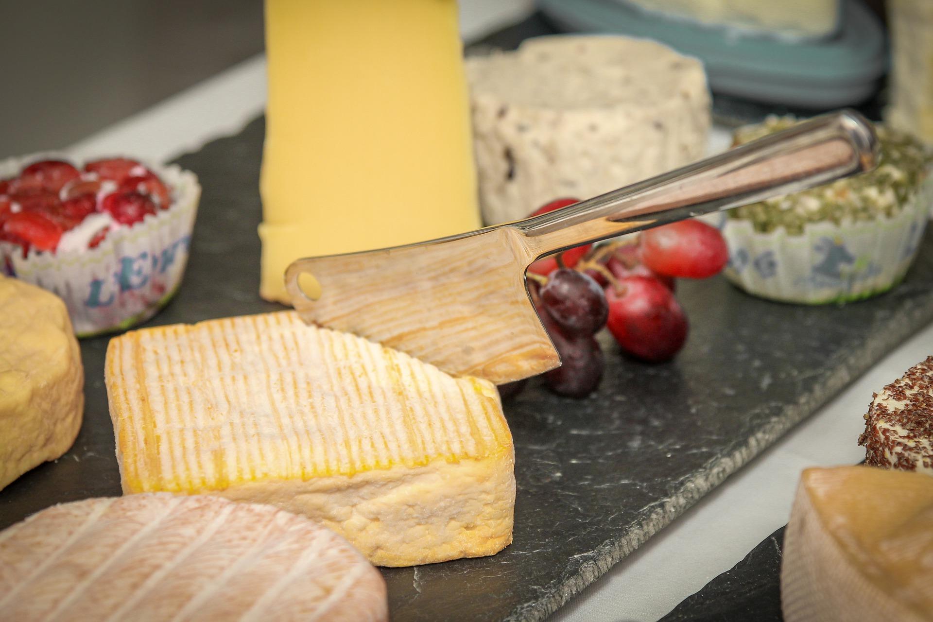 Eine Käseplatte mit unterschiedlichen Käsesorten, einem eckigen Weichkäse steckt ein Käsemesser, das aussieht wie ein Beil.