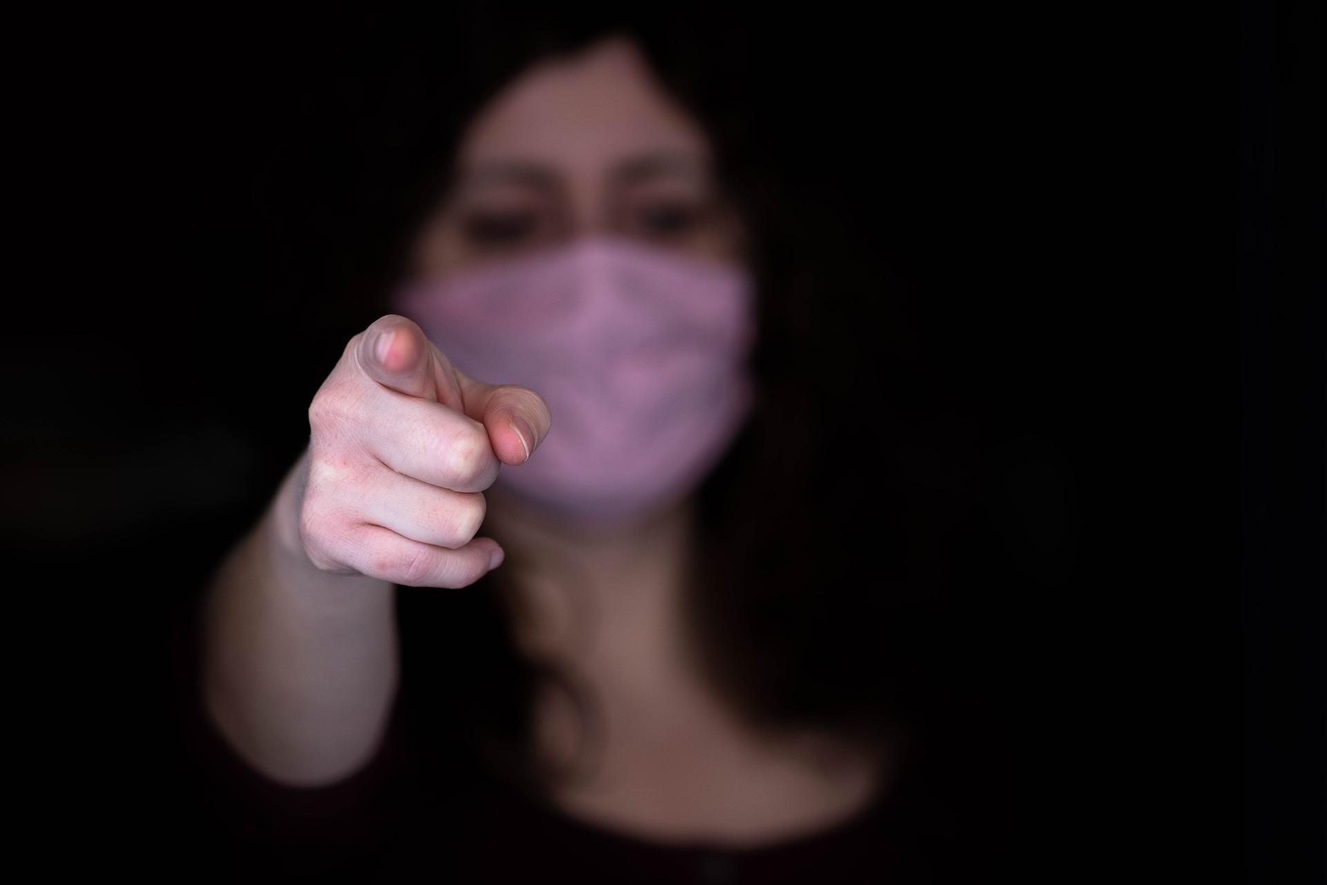 Eine Frau mit Mundnasenschutz zeigt mit dem Finger in die Kamera. Das Gesicht ist unscharf, nur die Hand ist scharfgestellt.