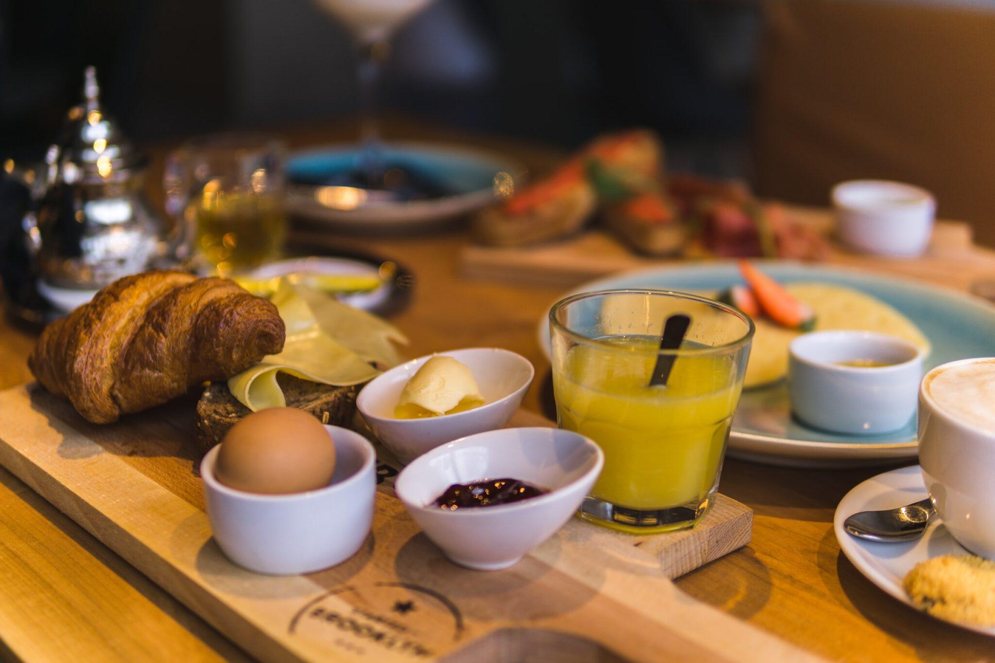 Ein gedeckter Frühstückstisch mit Orangensaft, Ei, Marmelade, Butter, Gipfeli und anderen Sachen.