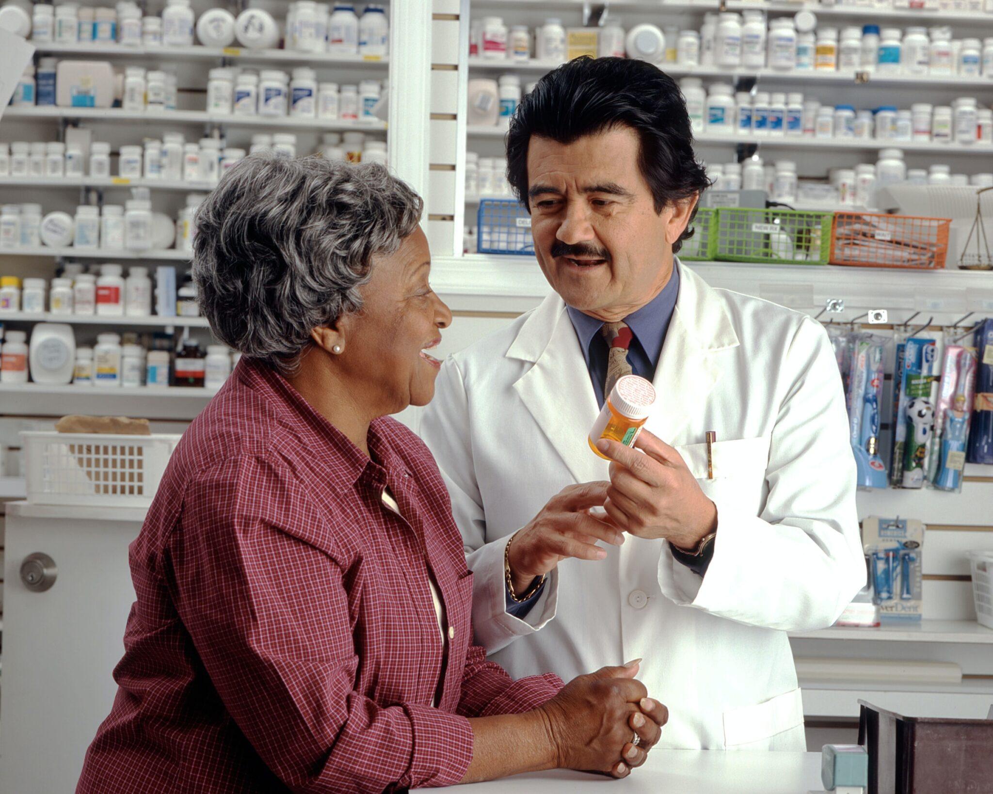 Eine ältere Dame bekommt ein Röhrchen Pillen von einem Apotheker im weissen Kittel. Beide sehen fröhlich aus
