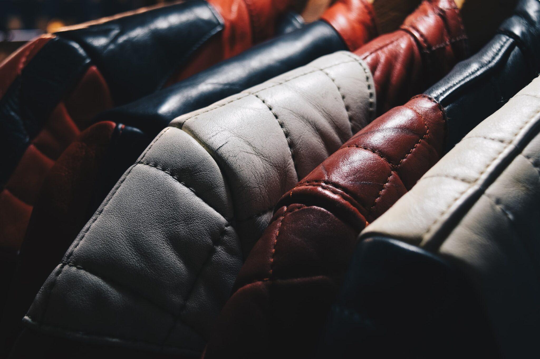 Eine Nahaufnahme von Schulterteilen von Lederjacken, die auf einer Kleiderstange hängen. Die Jacken sind schwarz, grau und rot.