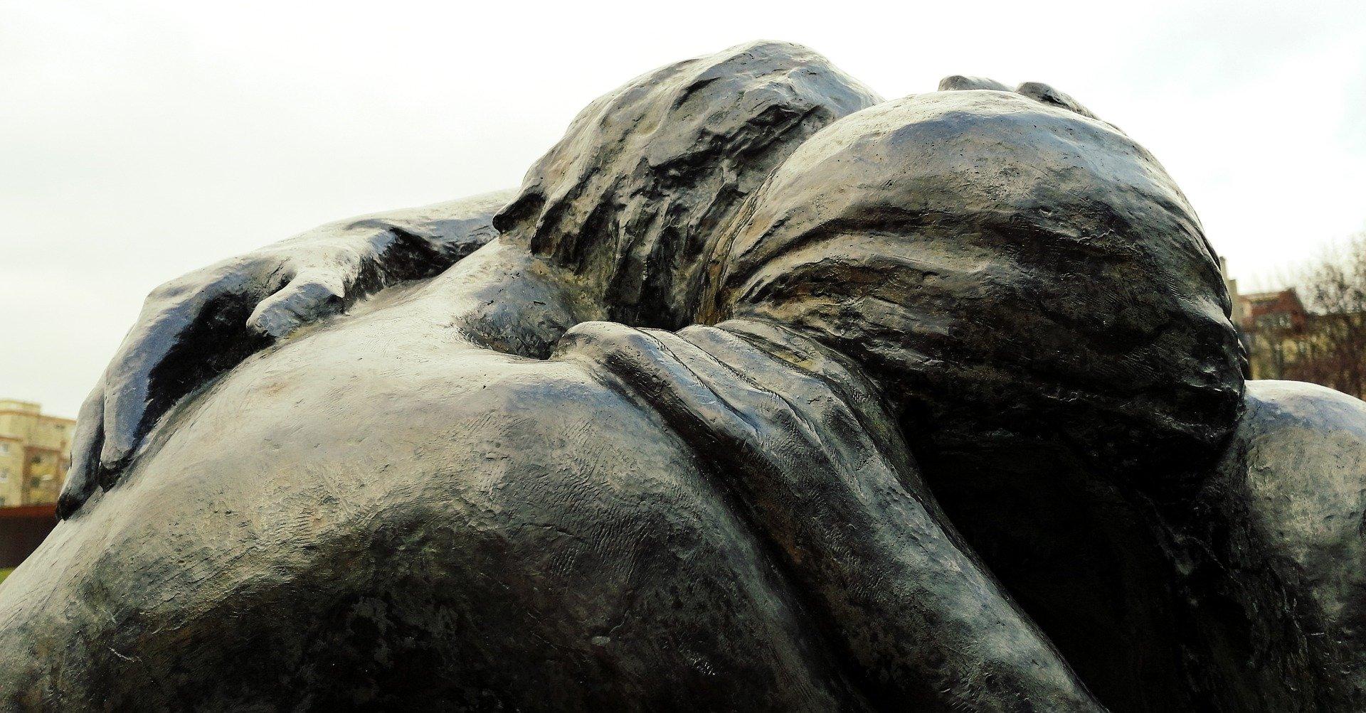 Nahaufnahme der Schulter-Kopf-Partie einer Statue, die 2 sich umarmende Menschen darstellt.