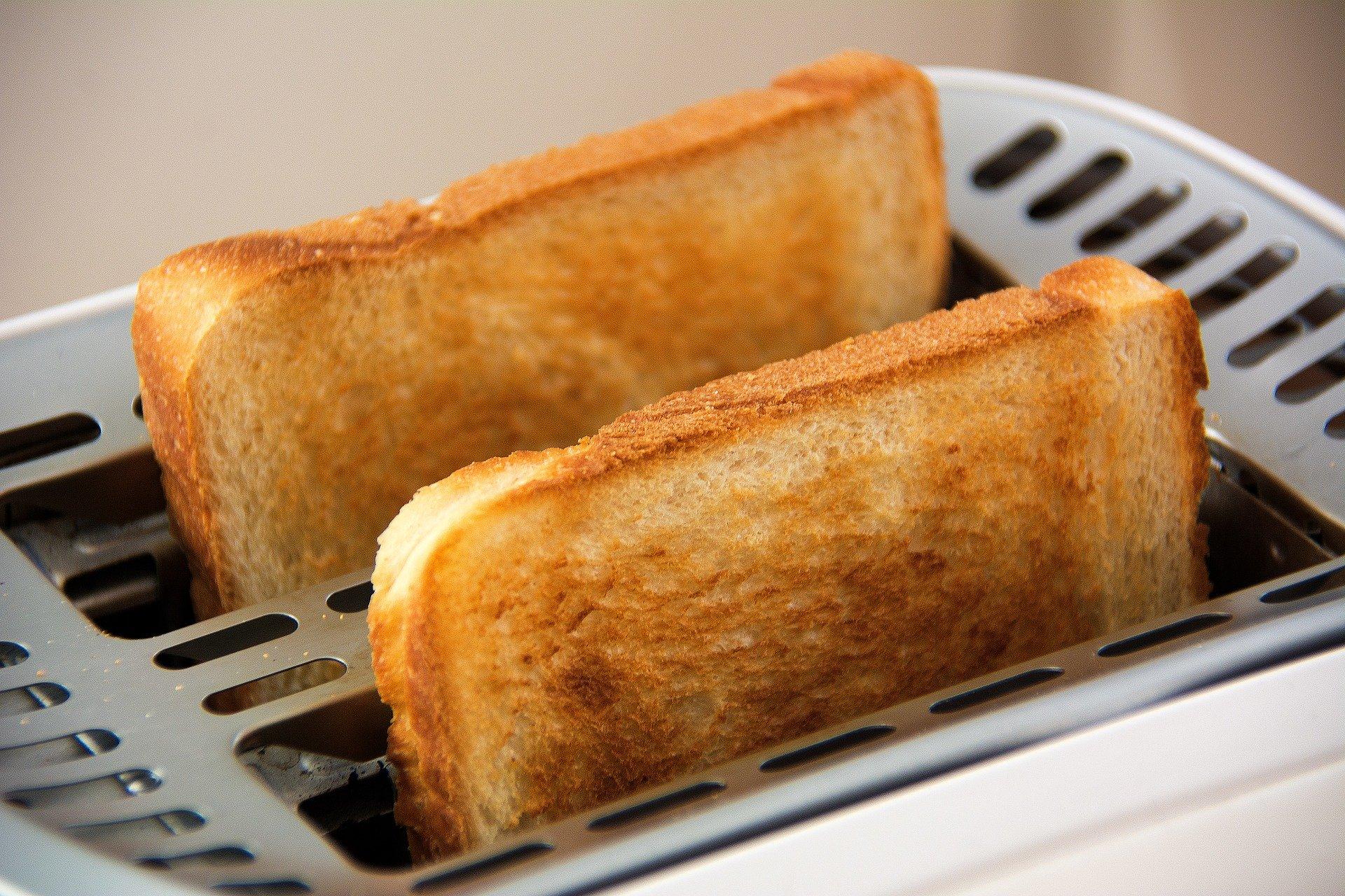 2 Scheiben goldbraunes Toastbrot kommen aus einem weiss-silbernen Toaster.