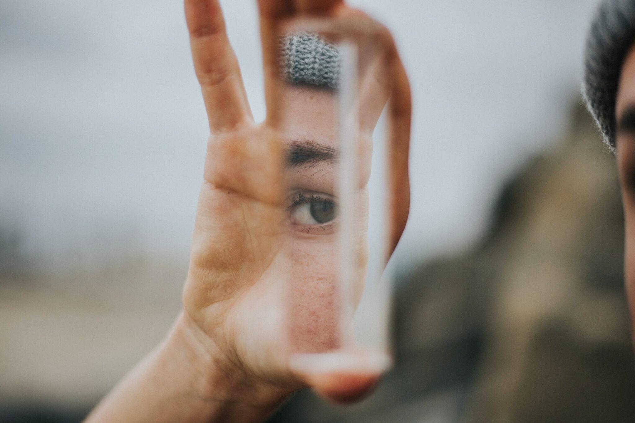 Eine Hand hält hochkant einen länglichen Spiegel, in dem sich das Auge einer Frau mit grauer Wollmütze spiegelt.