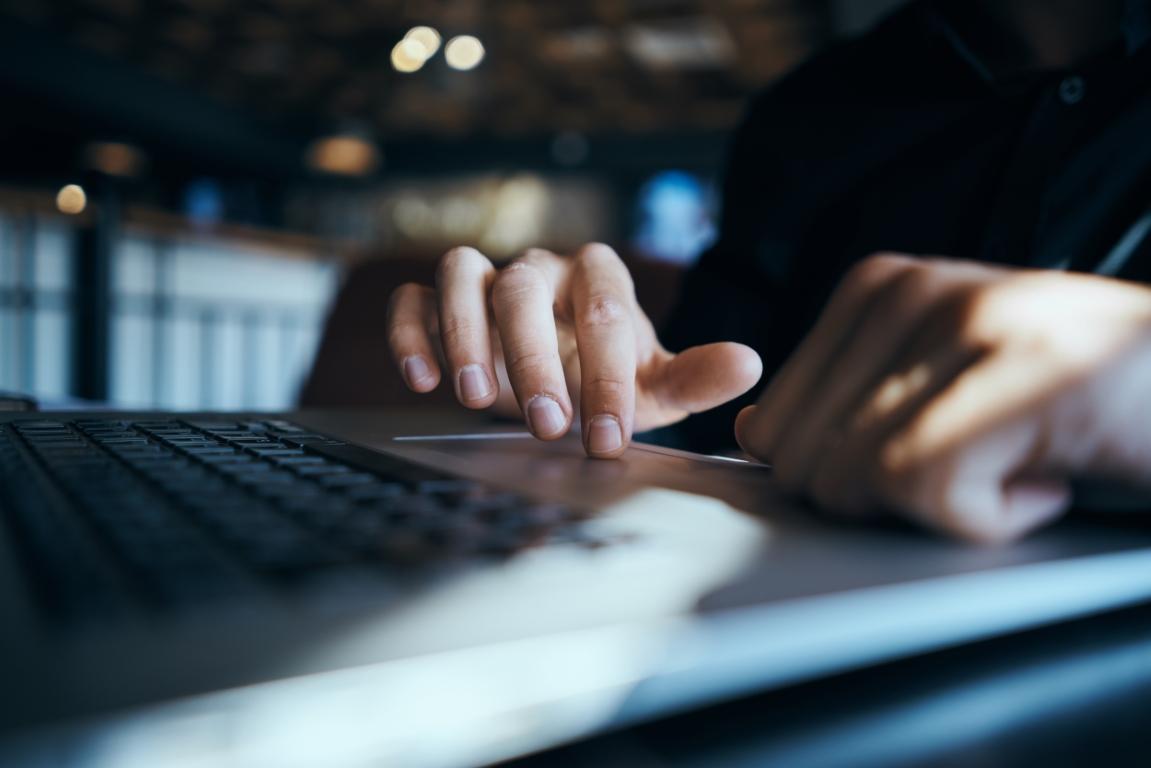 Nahaufnahme einer Laptop Tastatur, Hände bedienen ein Touchpad