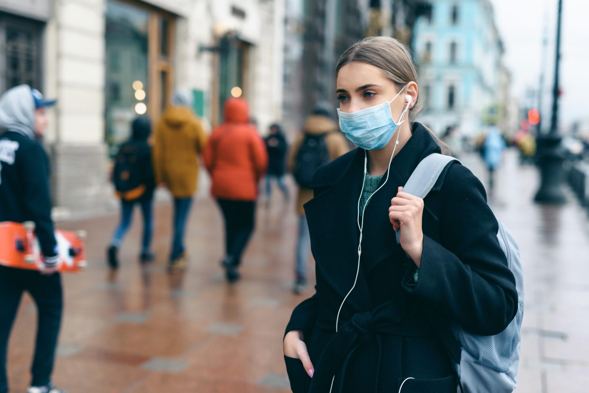 Bild einer jungen europäischen Frau mit Maske auf der Strasse in der Stadt.