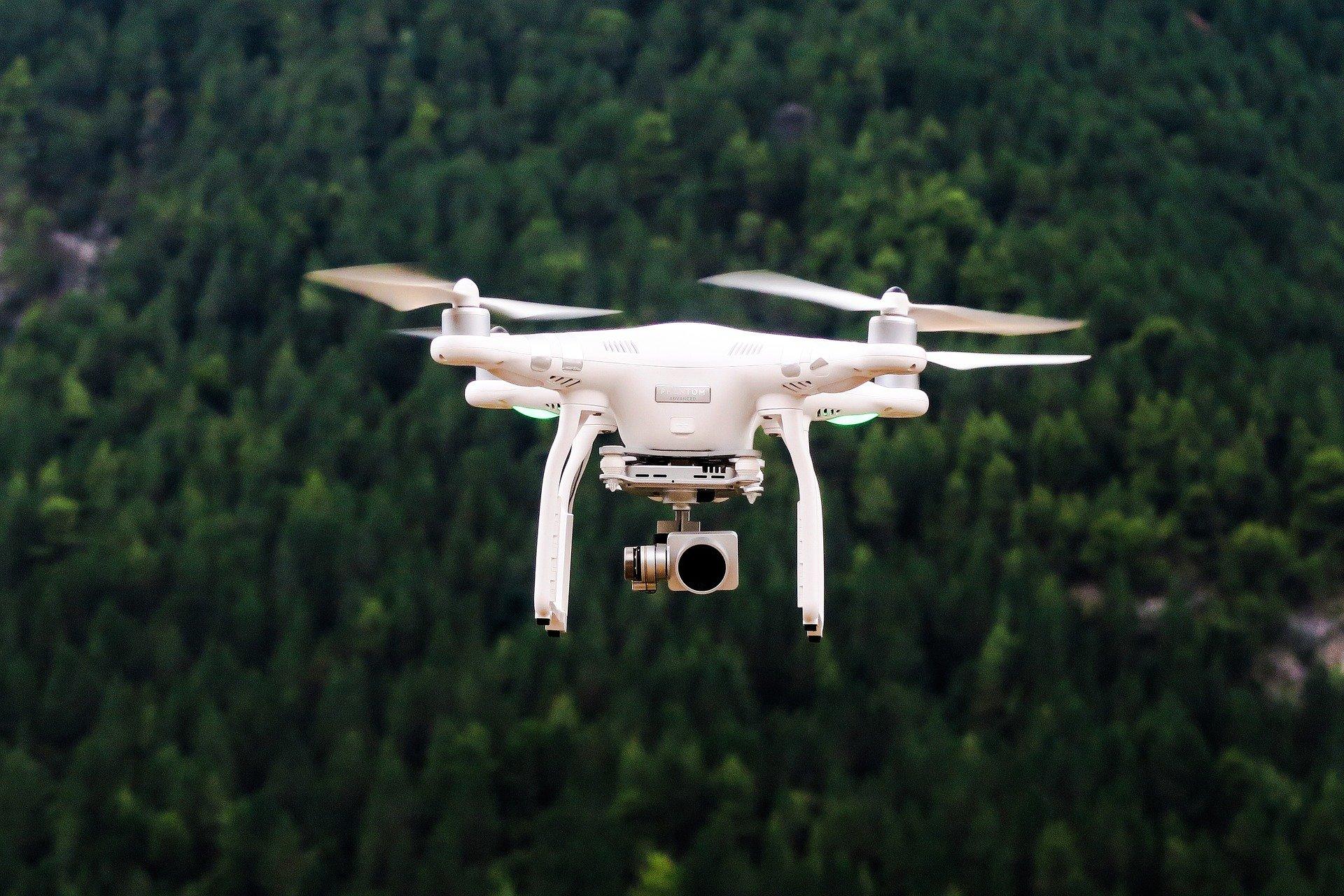 Ein Drohnenbild einer weissen Drohne über einem grünen Wald.