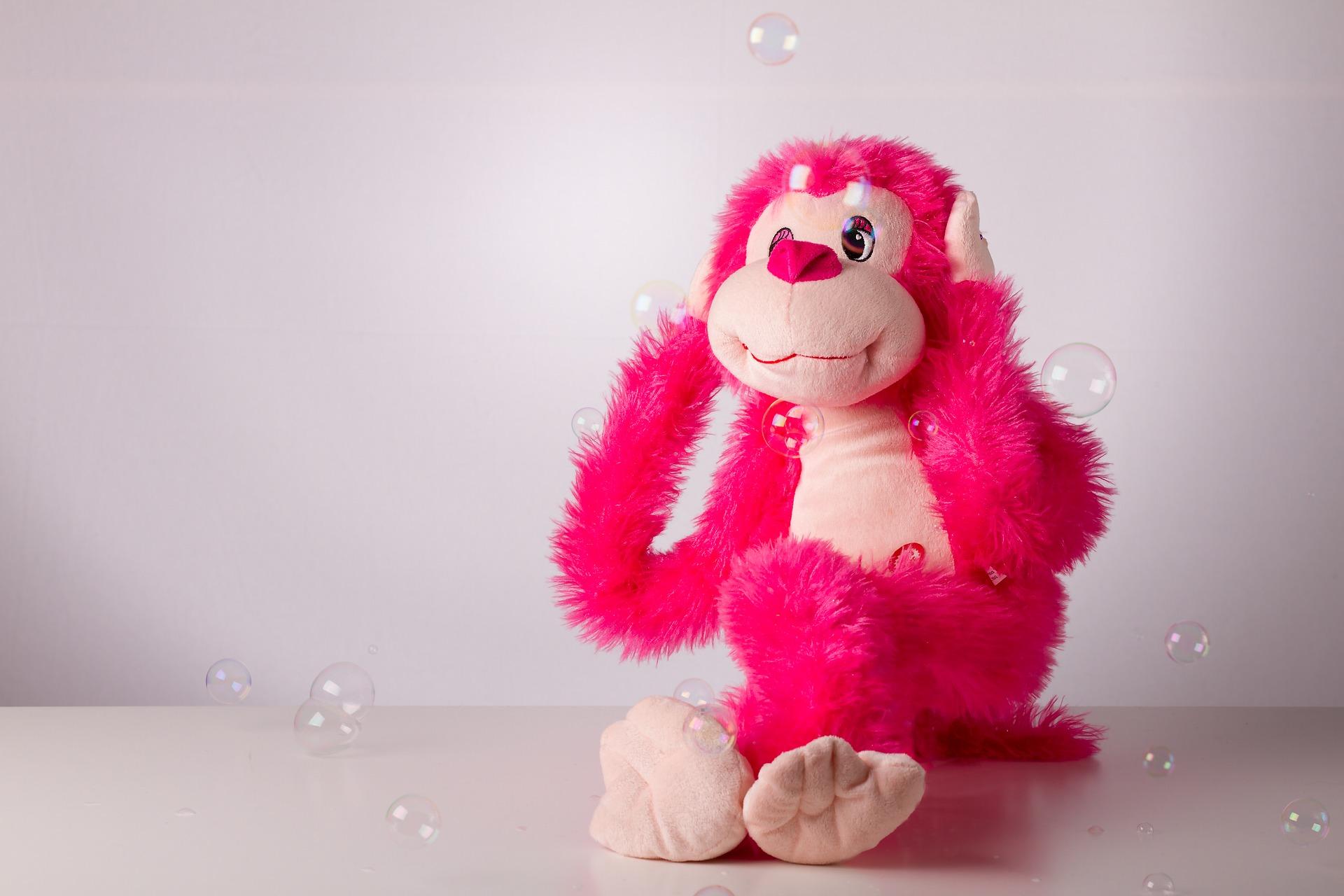 Ein pinkfarbener Plüschaffe hält sich die Ohren zu. Ausserdem sind Seifenblasen zu sehen.