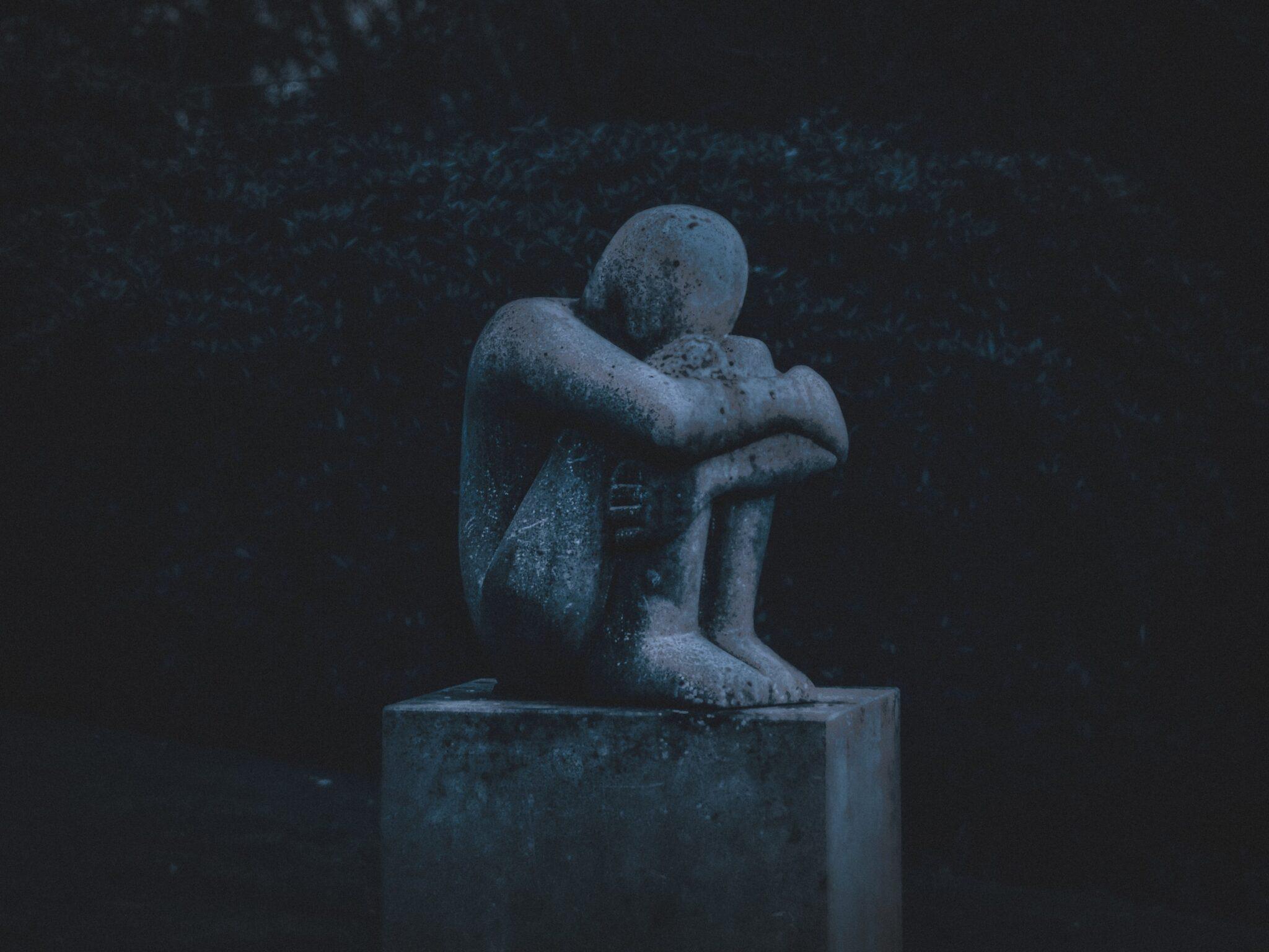 Eine zusammengekauert sitzende Statue.