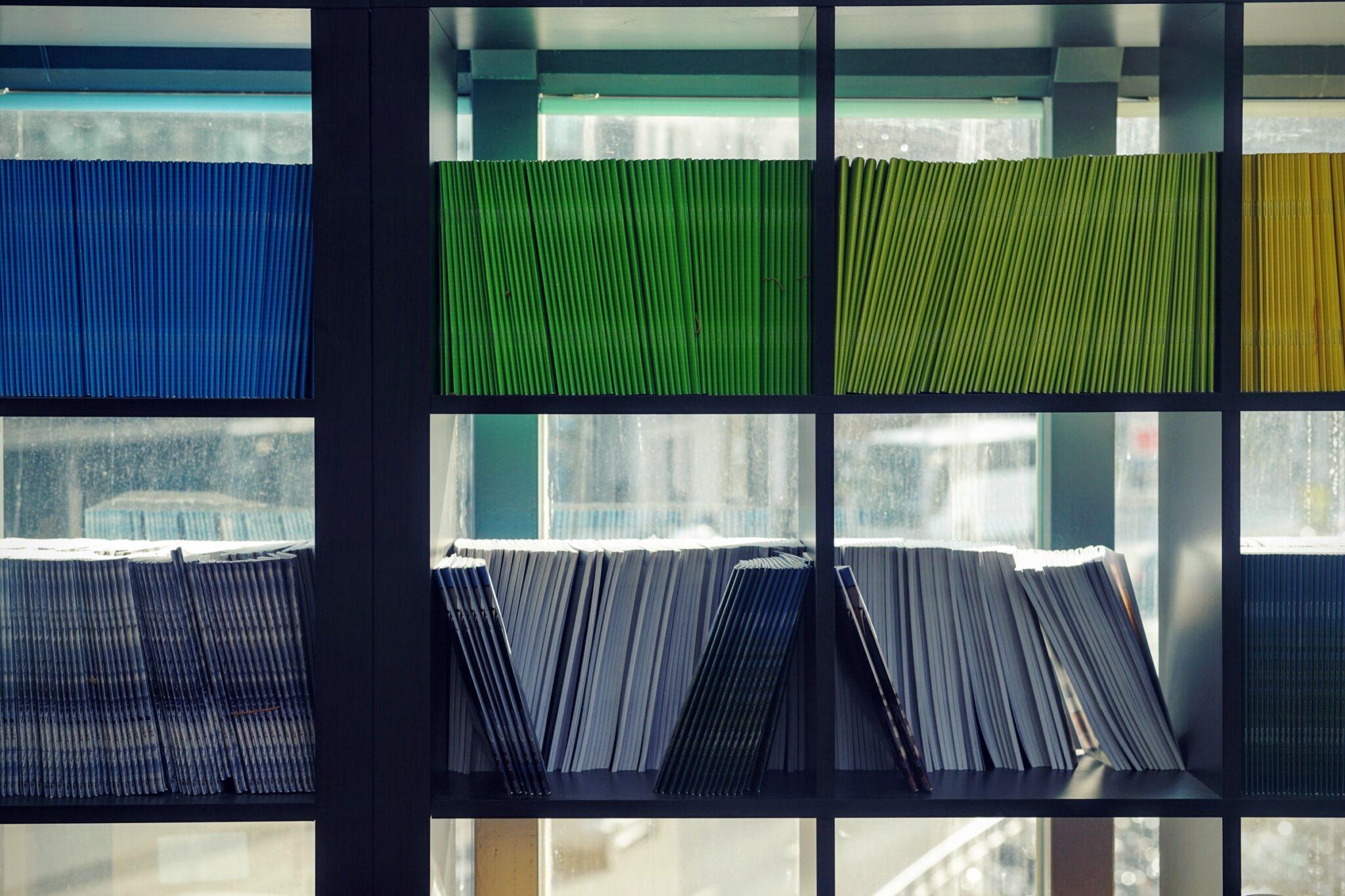 Ein schwarzes Regal mit quadratischen Fächern, in denen man nach Farben sortierte Zeitschriften sieht, in blau, grün, hellrgrün und schwarzweiss.