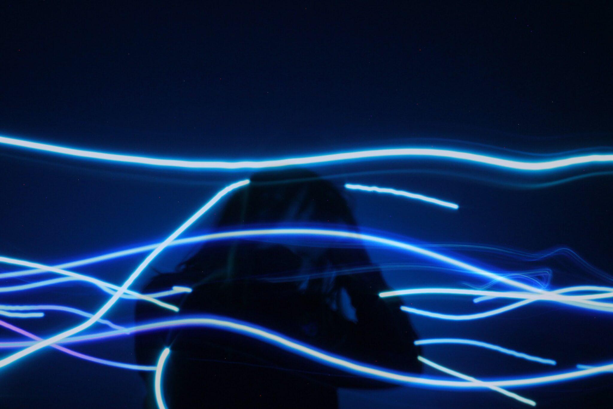 Schattenriss eines Menschen mit blauen Lichtstreifen um ihn herum.