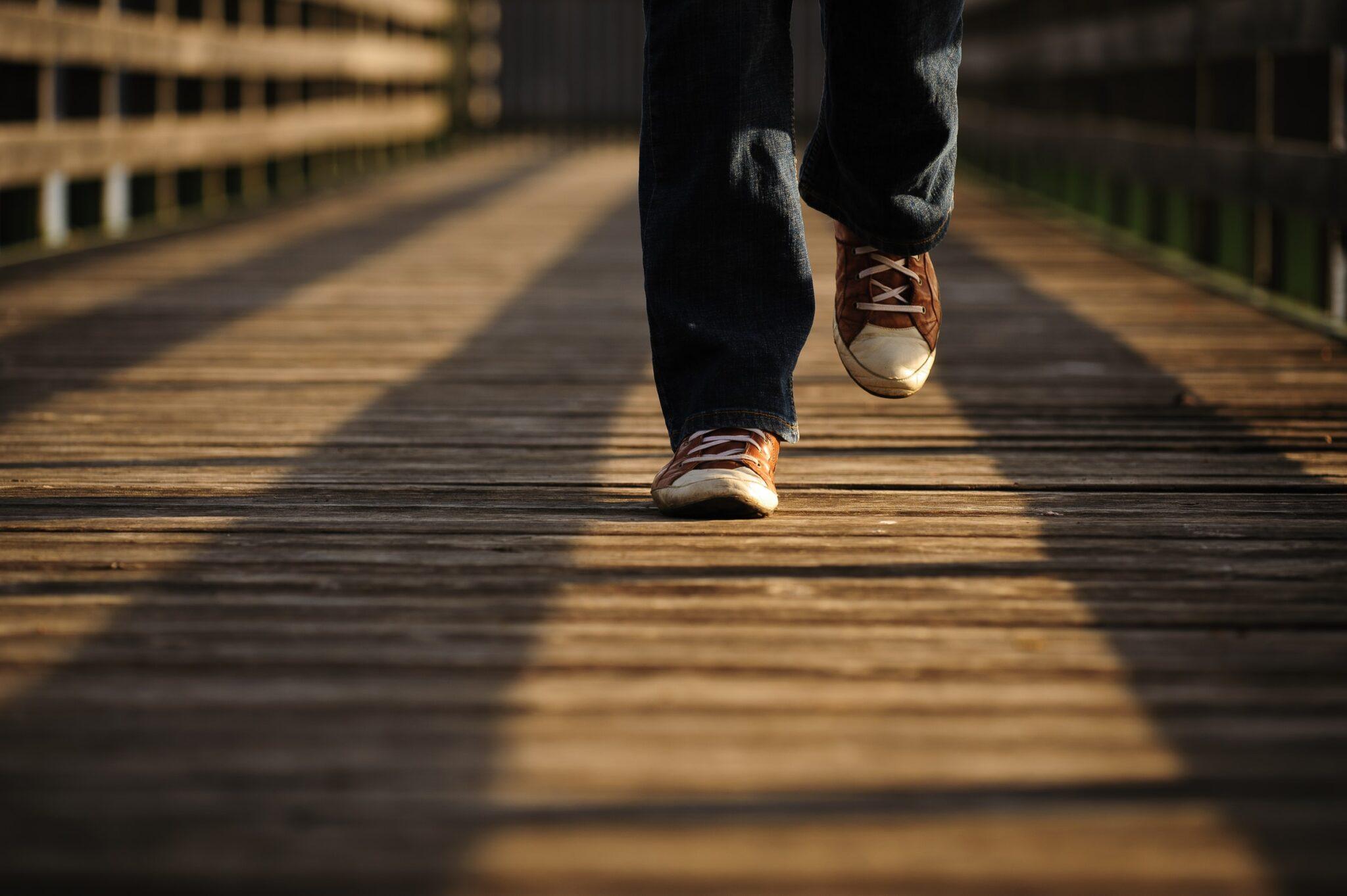 Füße in Sneakern, über Holzbohlen laufend