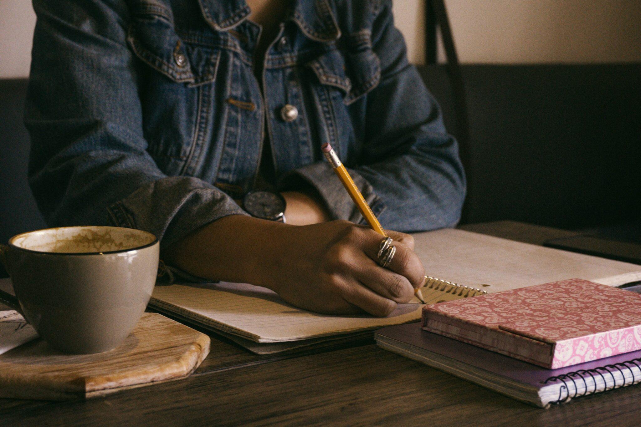 Eine Frau schreibt mit der Hand etwas in ein Notizbuch