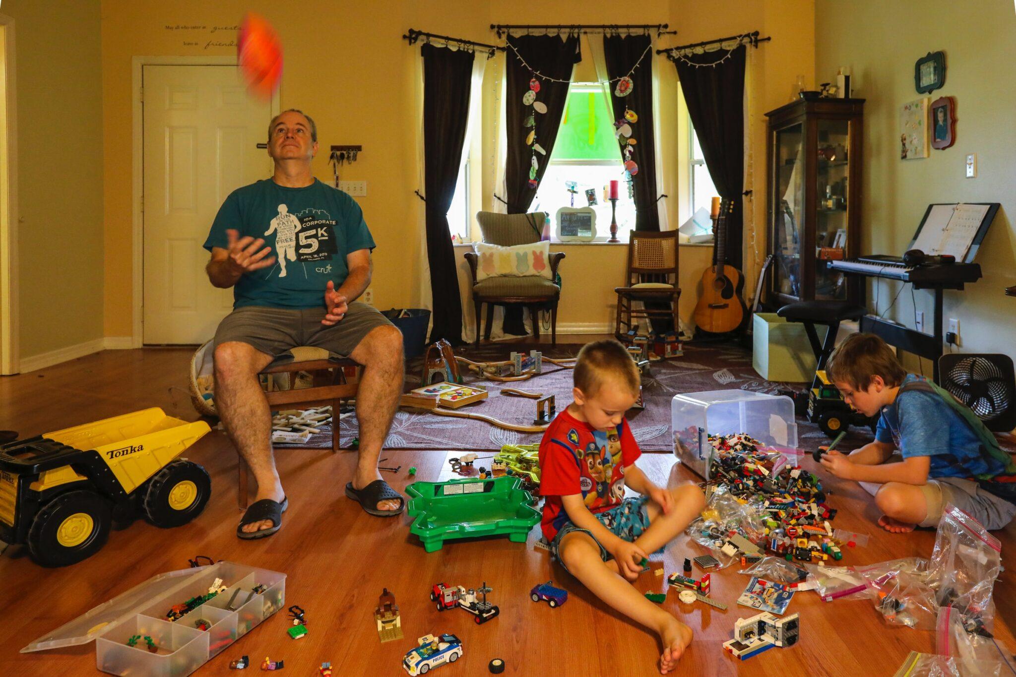 Kinder spielen im Wohnzimmer, ein Mann wirft etwas Rotes hoch.