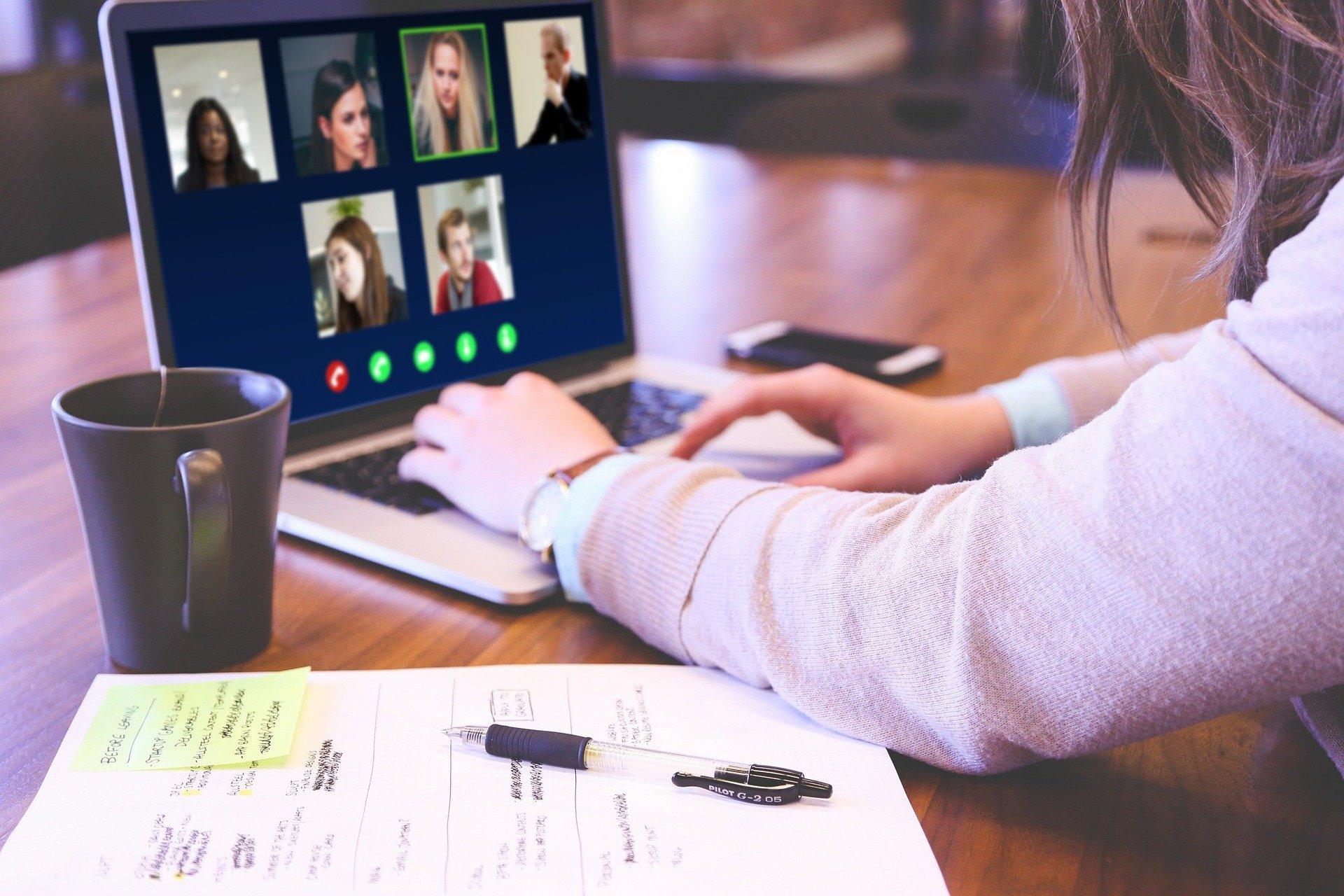 Ein Schreibtisch mit Unterlagen und einer Videokonferenz auf dem Laptop.
