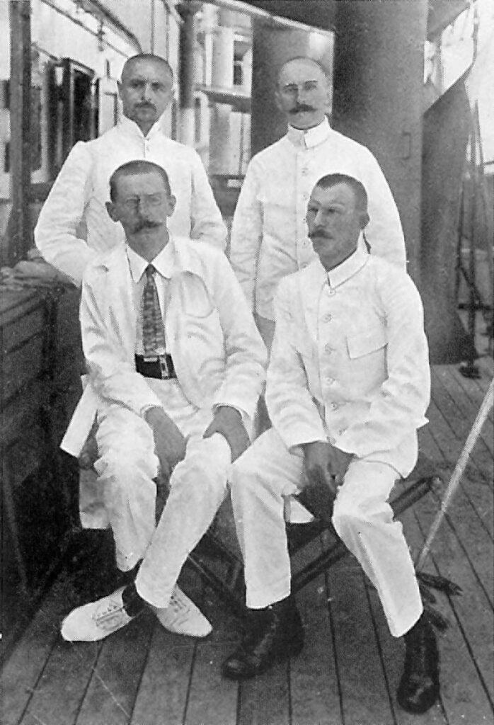 4 schnurrbärtige Männer in weissen Kitteln