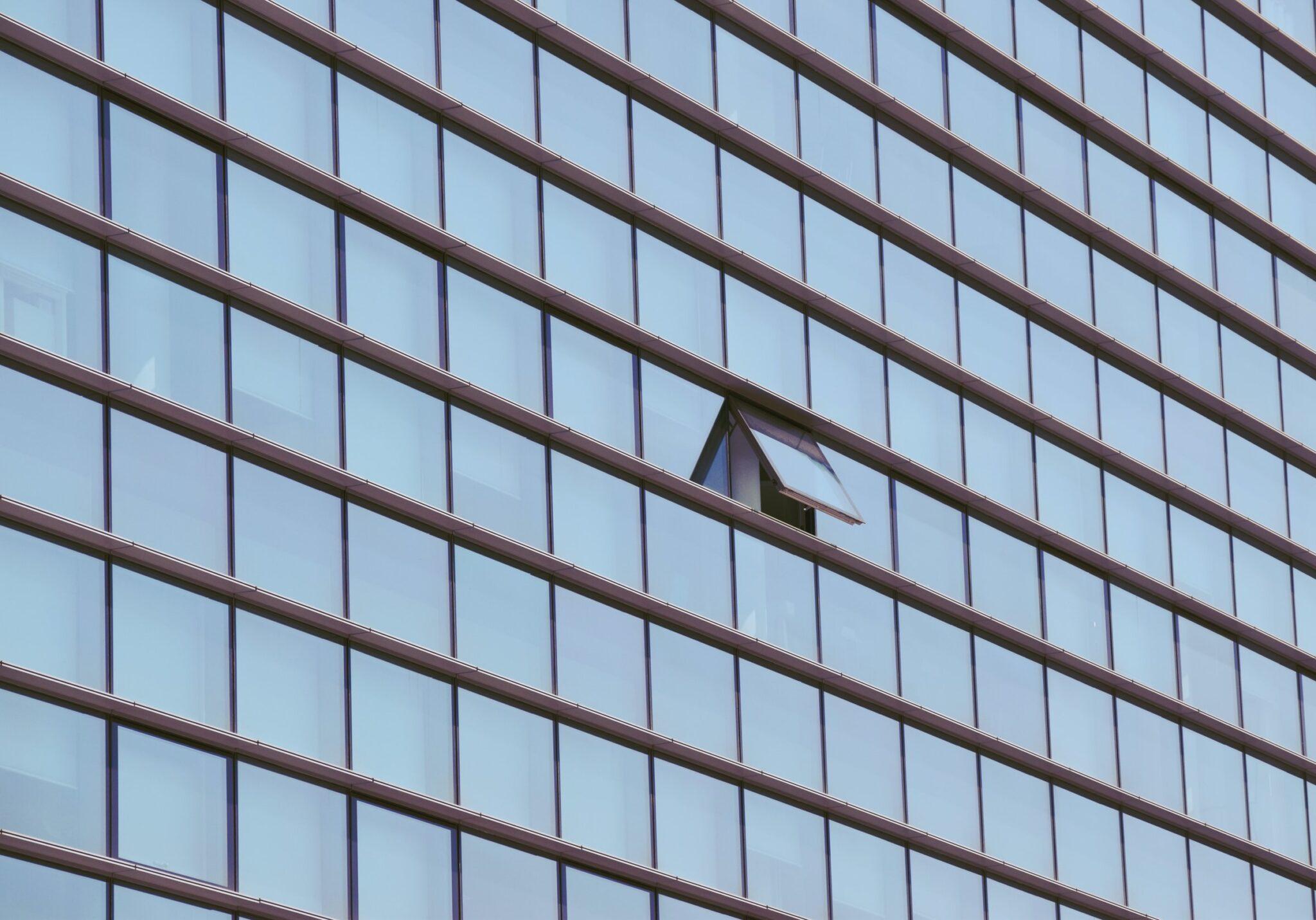 Glasfassade eines Bürogebäudes mit einem offenen Fenster.