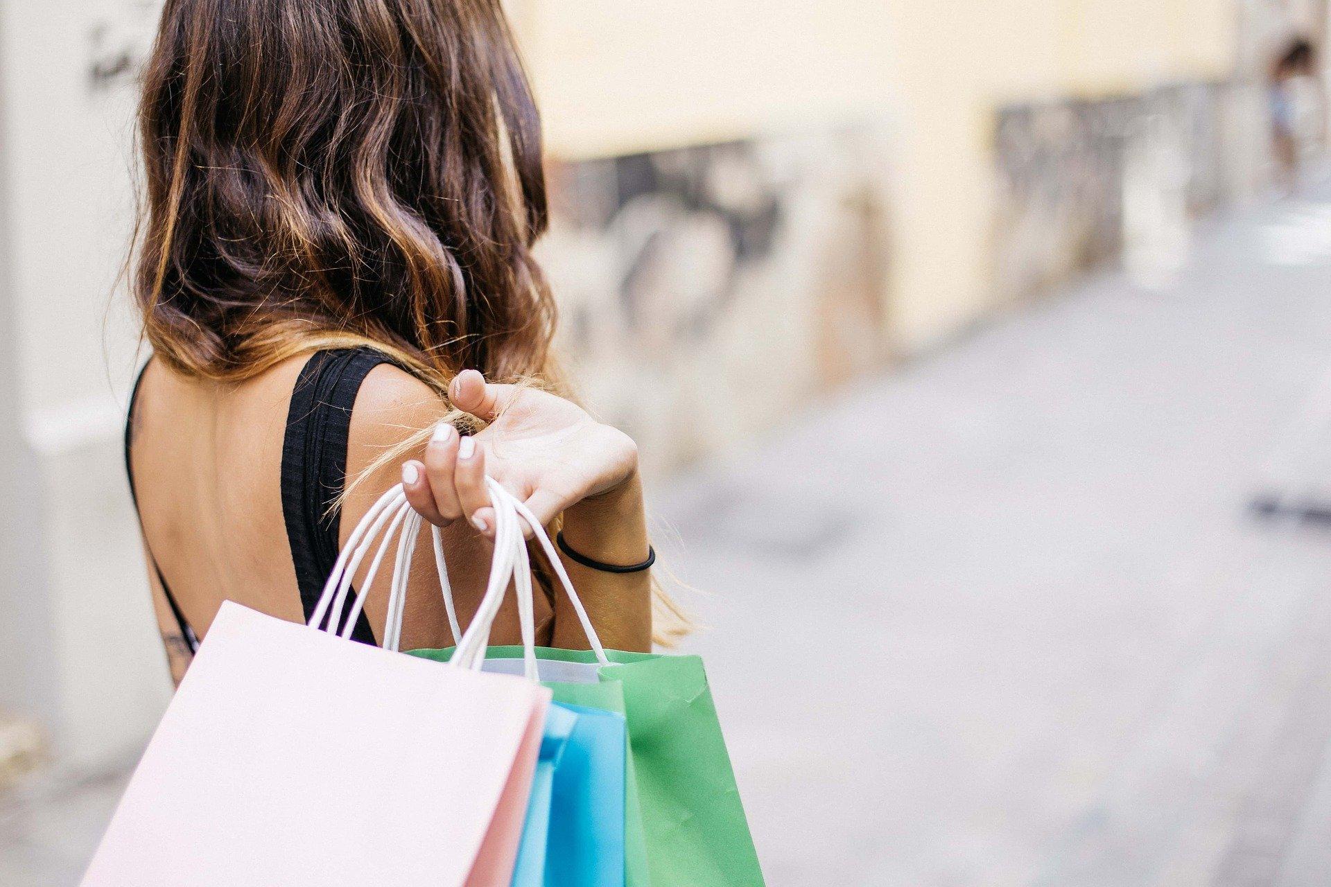 Frau mit Einkaufsstüten über der Schulter.