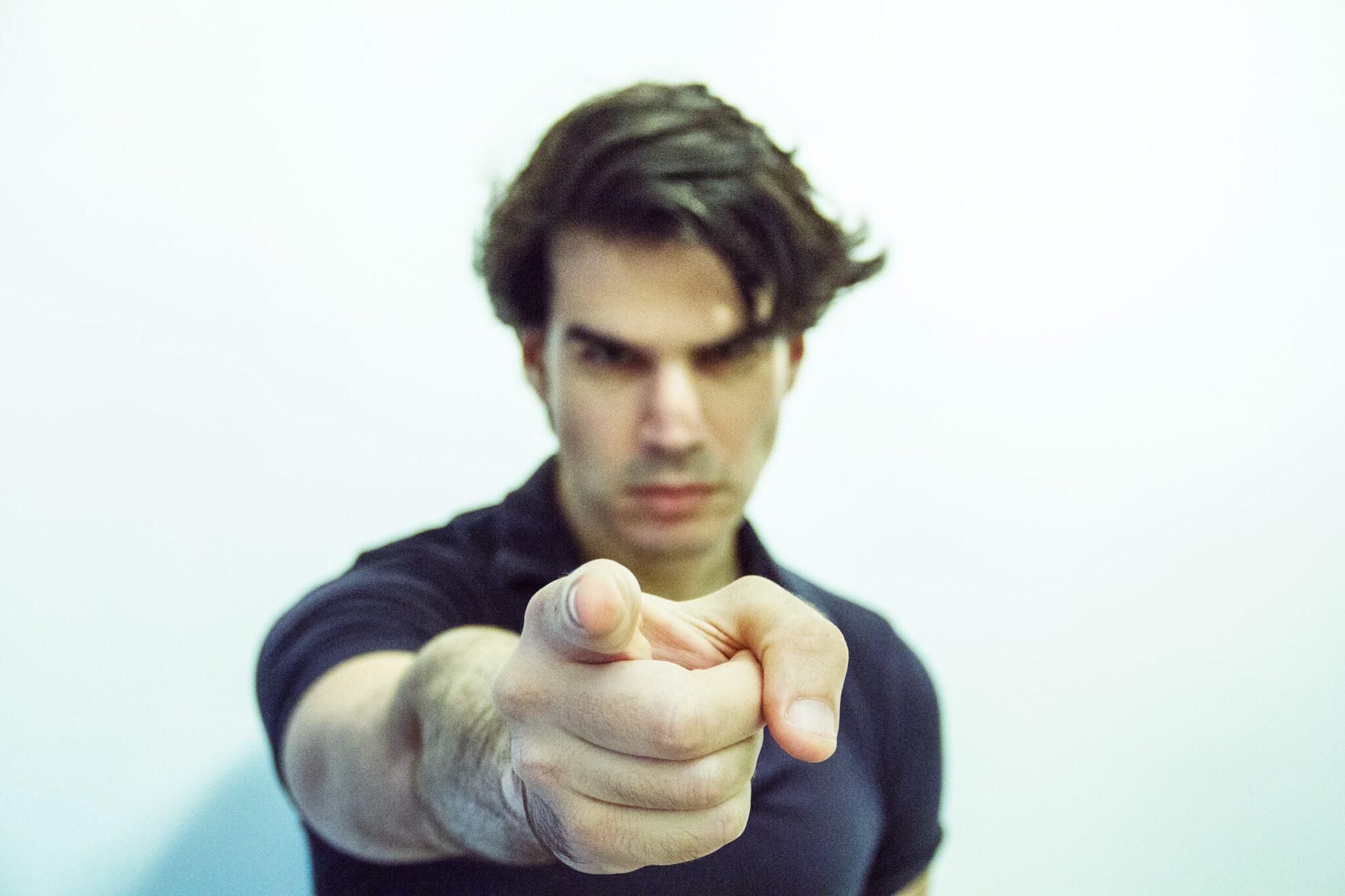 Ein Mann zeigt wütend mit dem Finger auf den Betrachter des Bildes