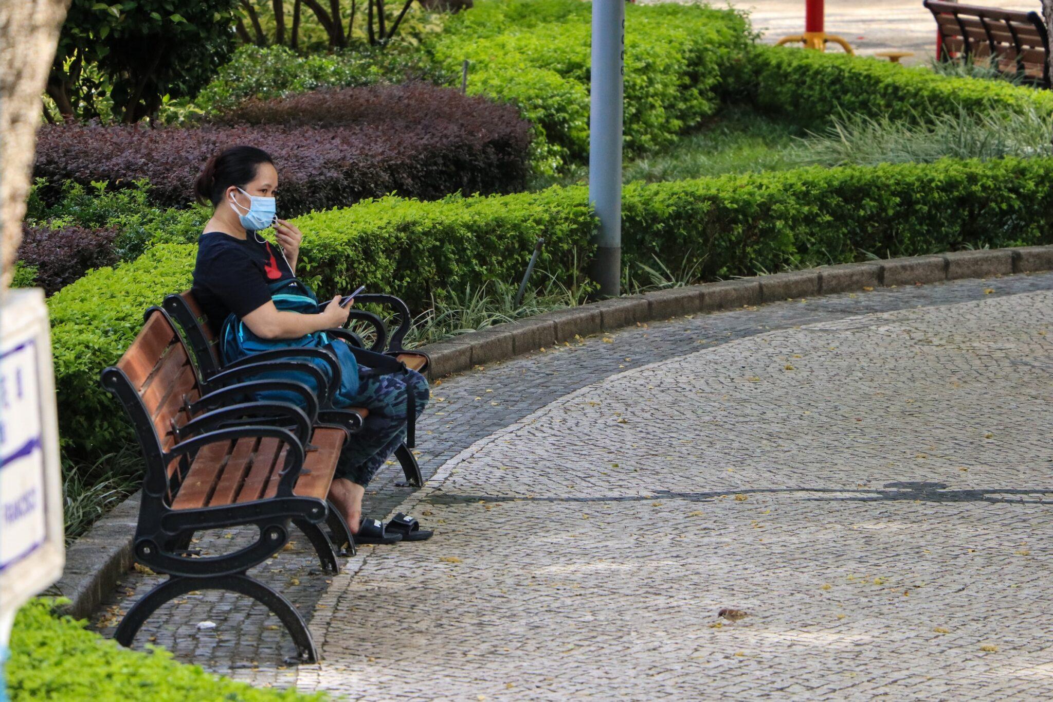 EIne Frau sitzt mit Mund-Nasen-Bedeckung auf einer Bank im Freien.