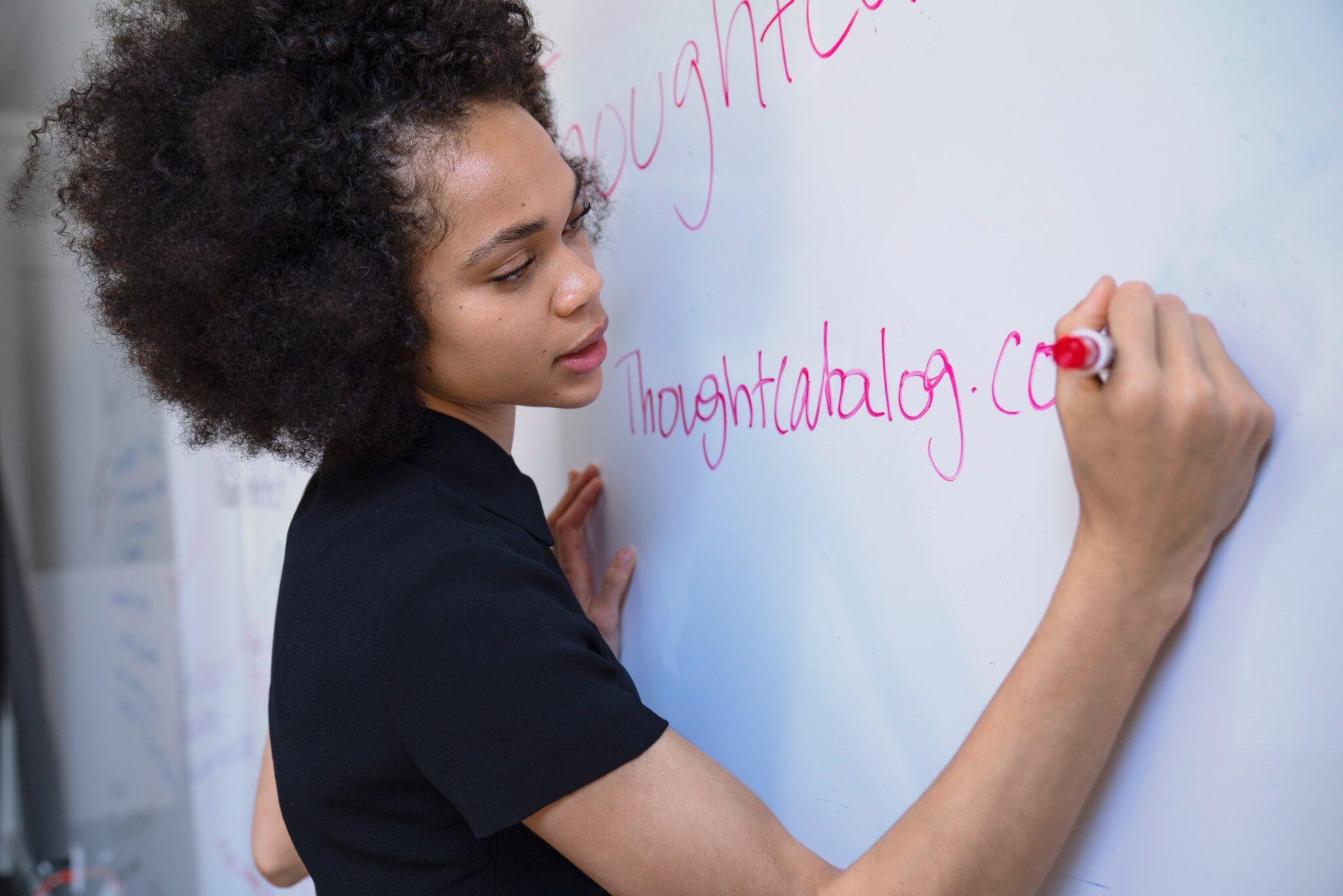 Eine Frau schreibt etwas auf ein Whiteboard.