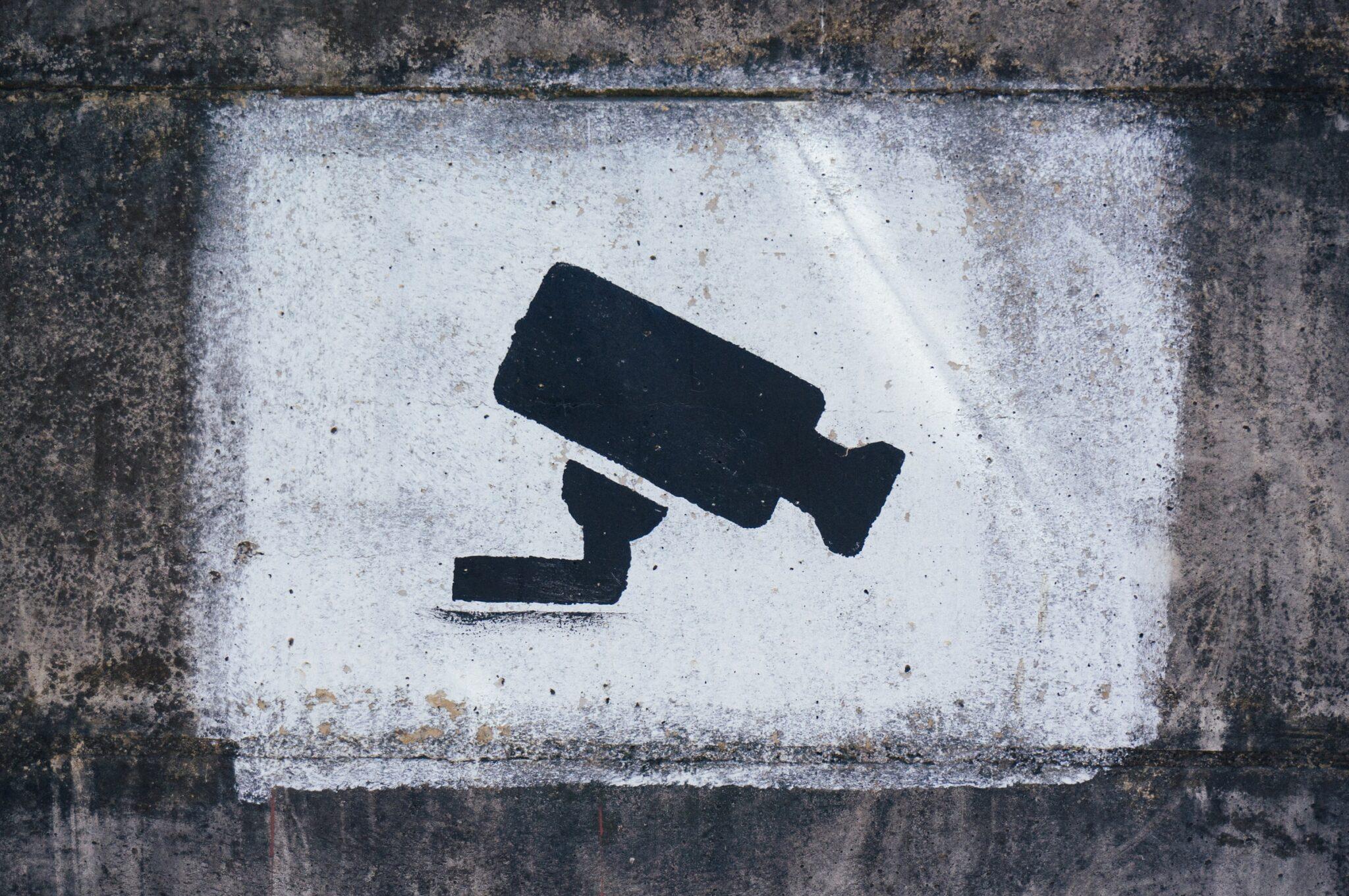 Eine stilisierte Überwachungskamera, die auf eine Wand gesprüht ist.