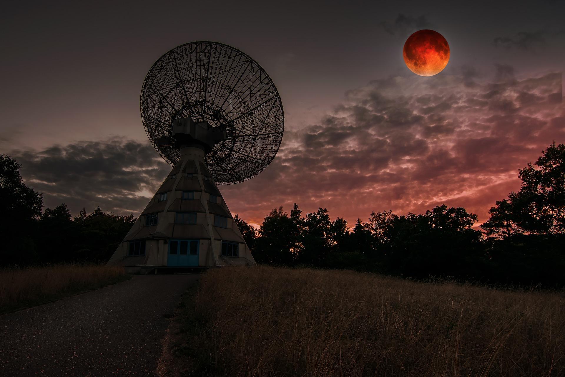 Radioteleskop-Antenne vor rötlich dunklem Himmel mit rotleuchtendem Mond