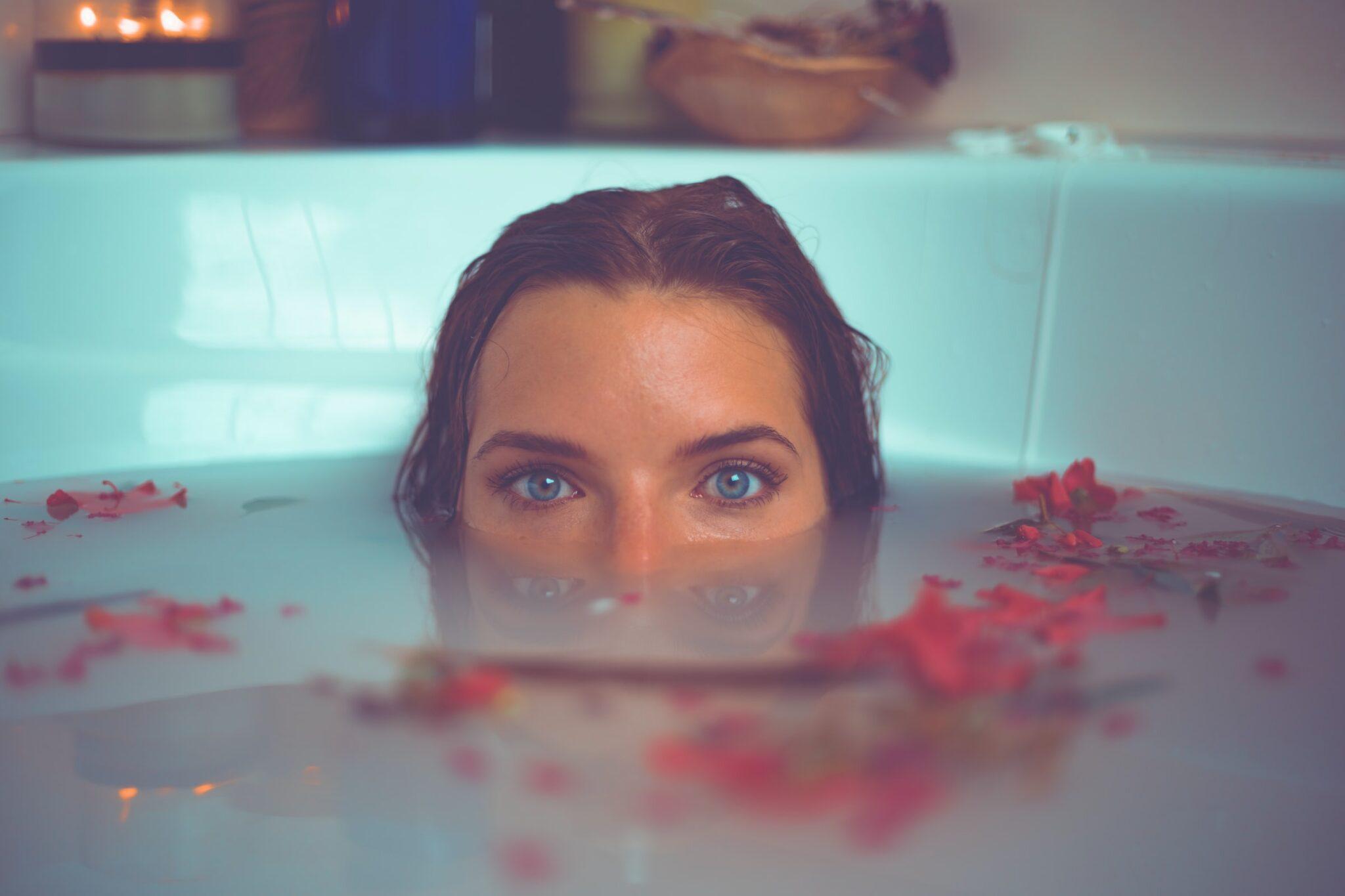 Frau mit Blüten in der Badewanne mit dem Gesicht halb unter Wasser