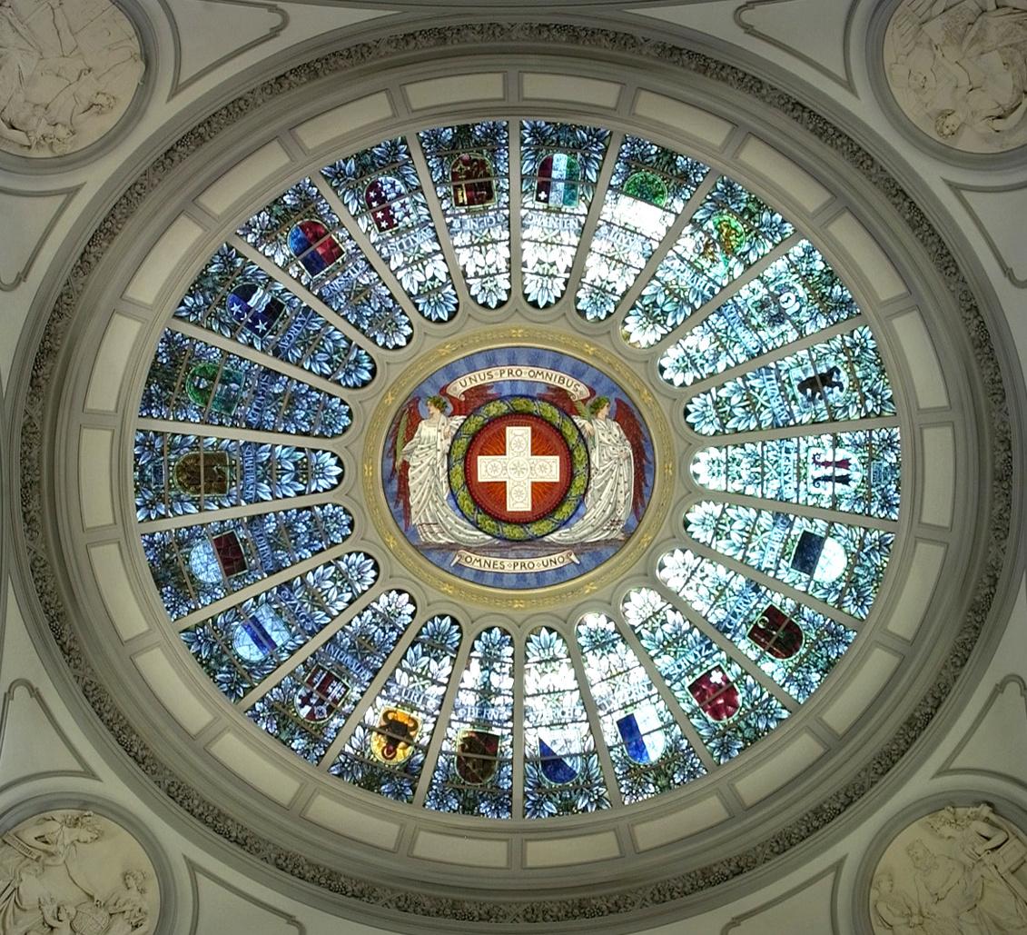"""Gläserne Kuppel mit Schweizer Flagge in der Mitte und den Wappen der Kantone aussen im Kreis angeordnet. über der Flagge steht """"Uns pro ominibus"""" und unter der flagge """"Omens pro uno""""."""
