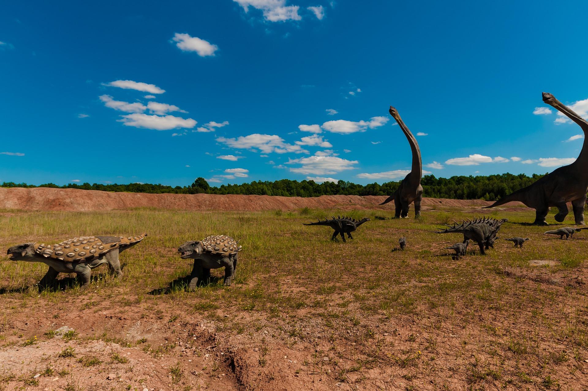 Illustration mit grossen und kleineren Dinosauriern auf einer Steppe.