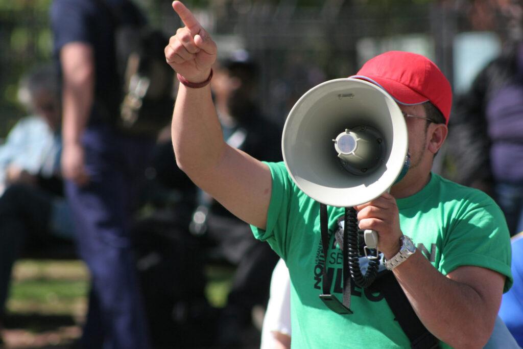 Mann mit grünem T-Shirt ruft etwas mit einem Megaphon an einem öffentlichen Ort.