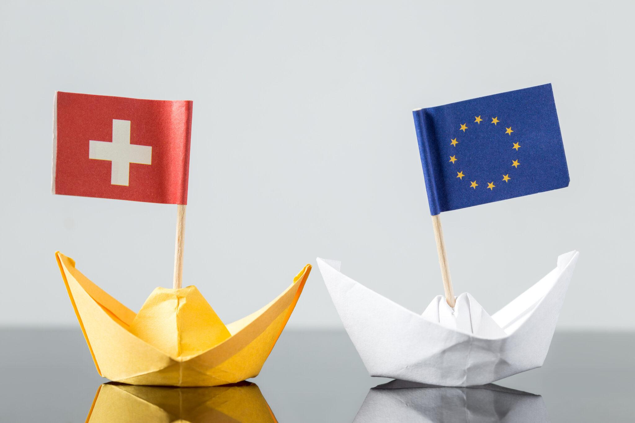 papierschiff mit schweizer und europäischer flagge