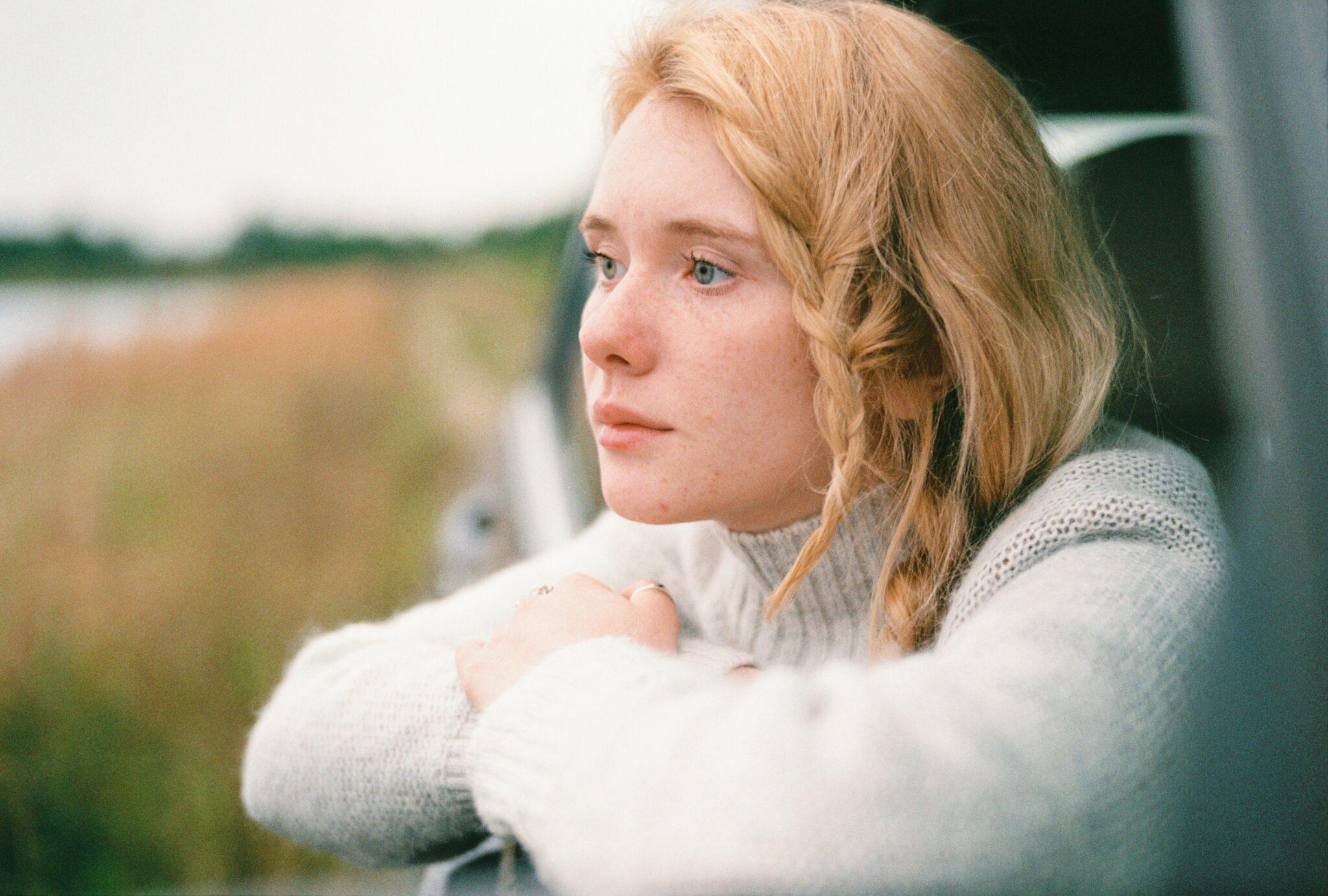 Eine blonde junge Frau schaut nachdenklich aus einem Auto auf ein Feld hinaus